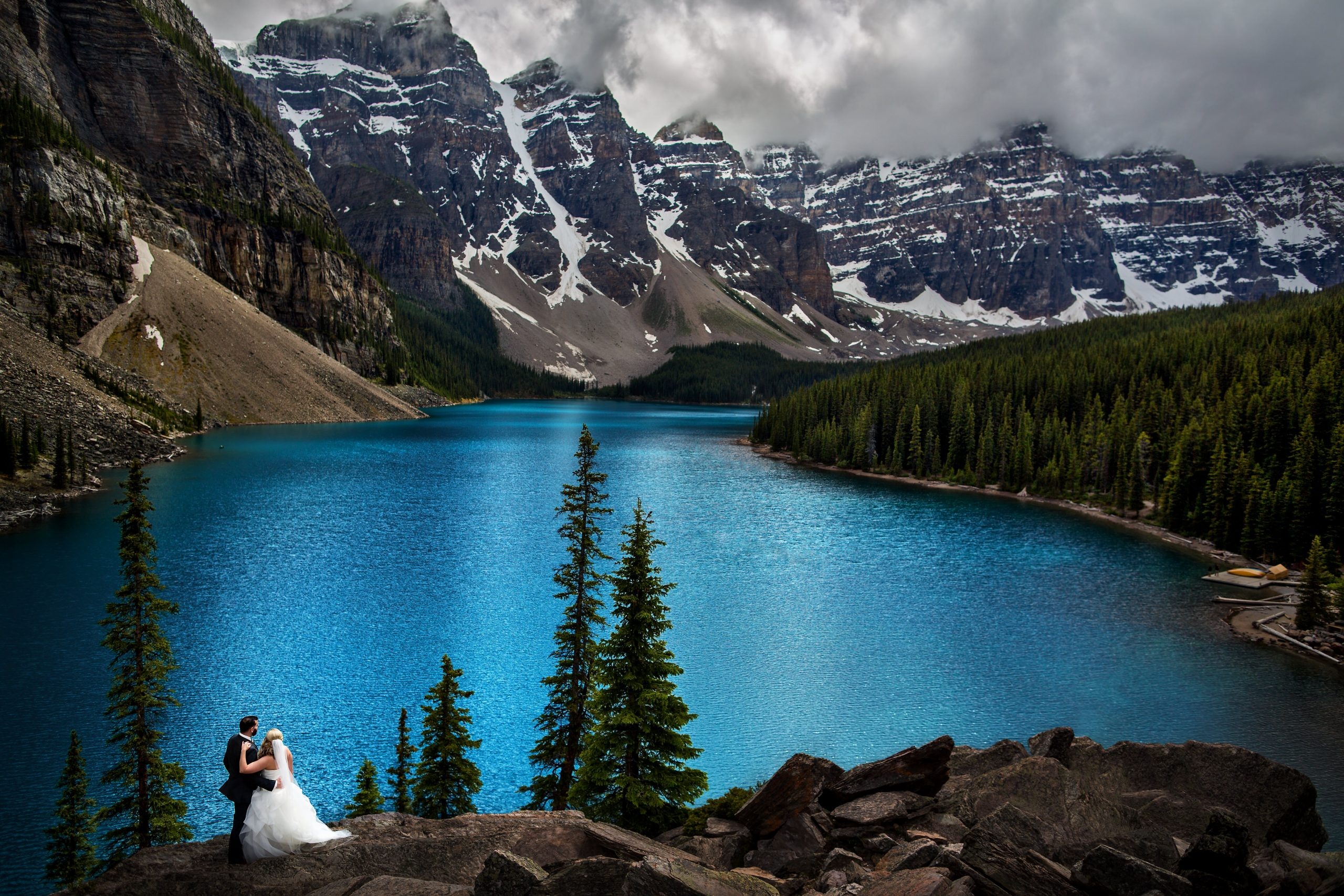 Bride and groom look over lake and forest, mountain landscape