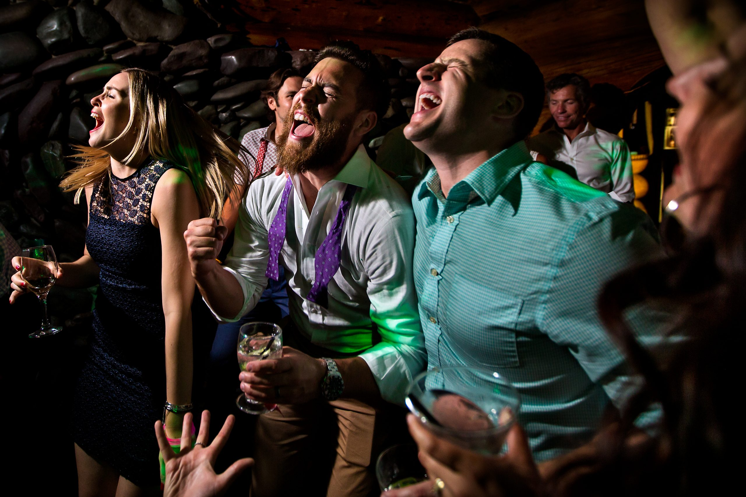 Partygoers close their eyes as they sing passionately