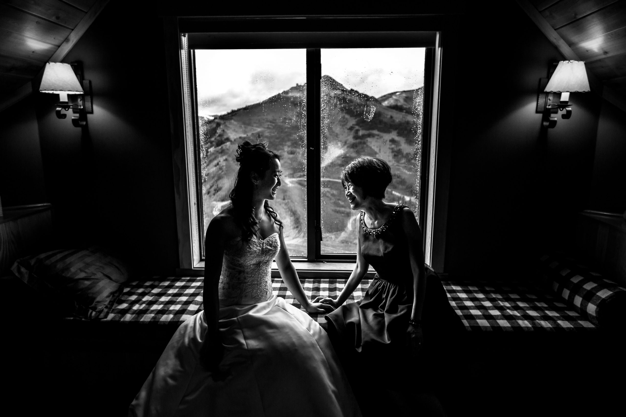 Bride sits with woman in front of window opening to mountain view