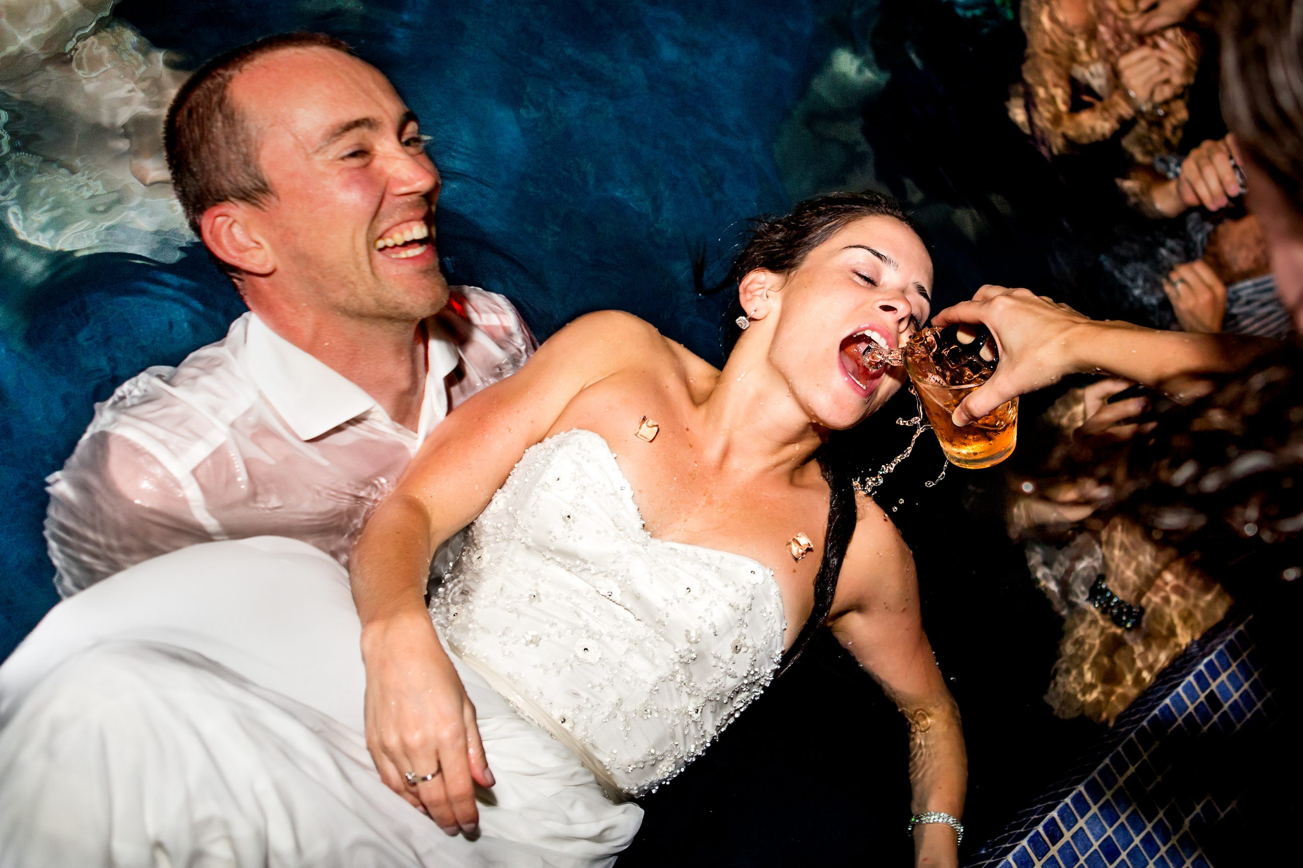 Bride has drink poured into her mouth as she is held by a man in a pool