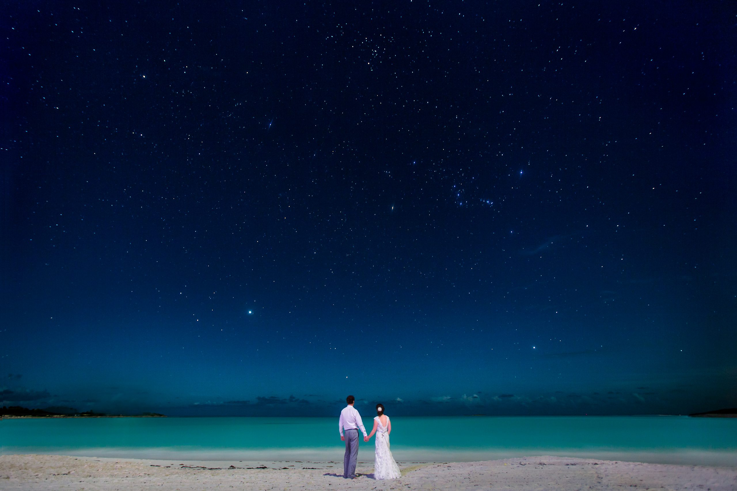 Bride and groom staring out into Sandals Emerald Bay on a starry night