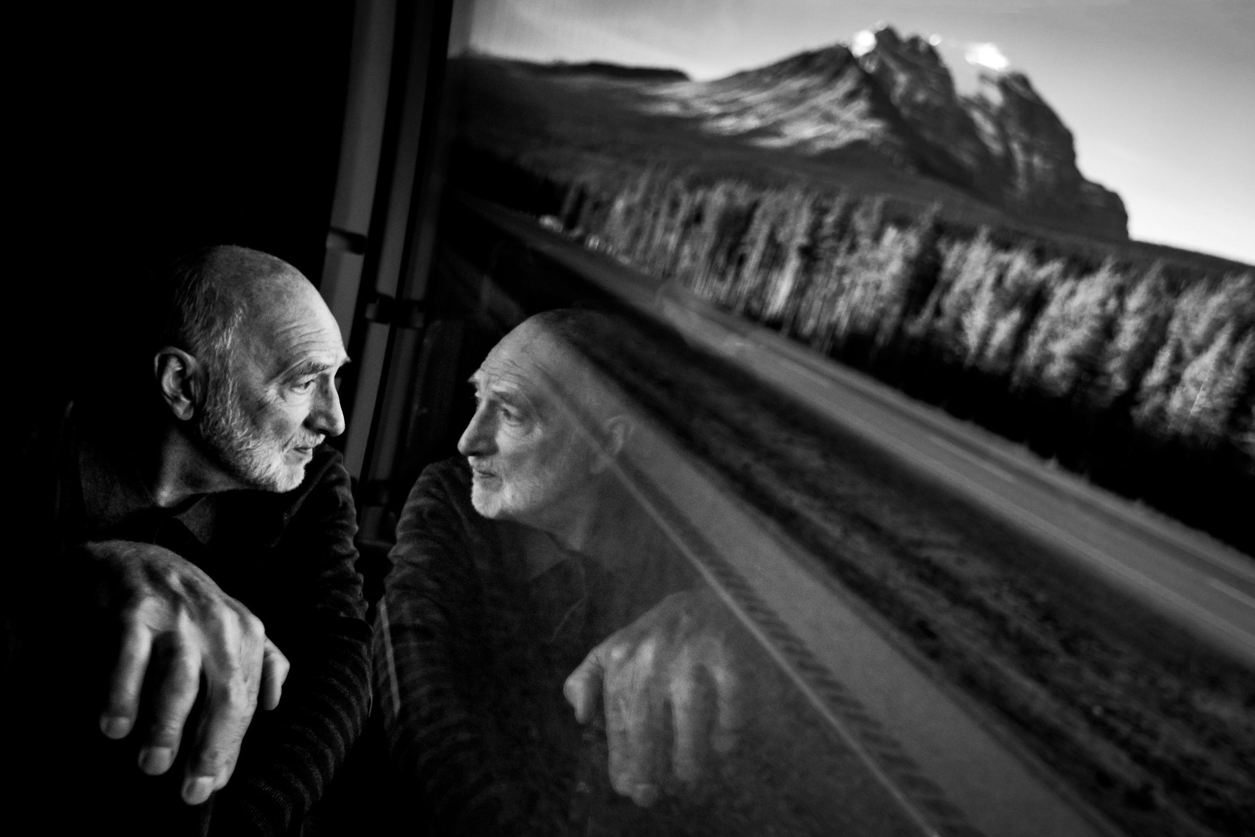 Man looks out window to mountain environment and sees his reflection