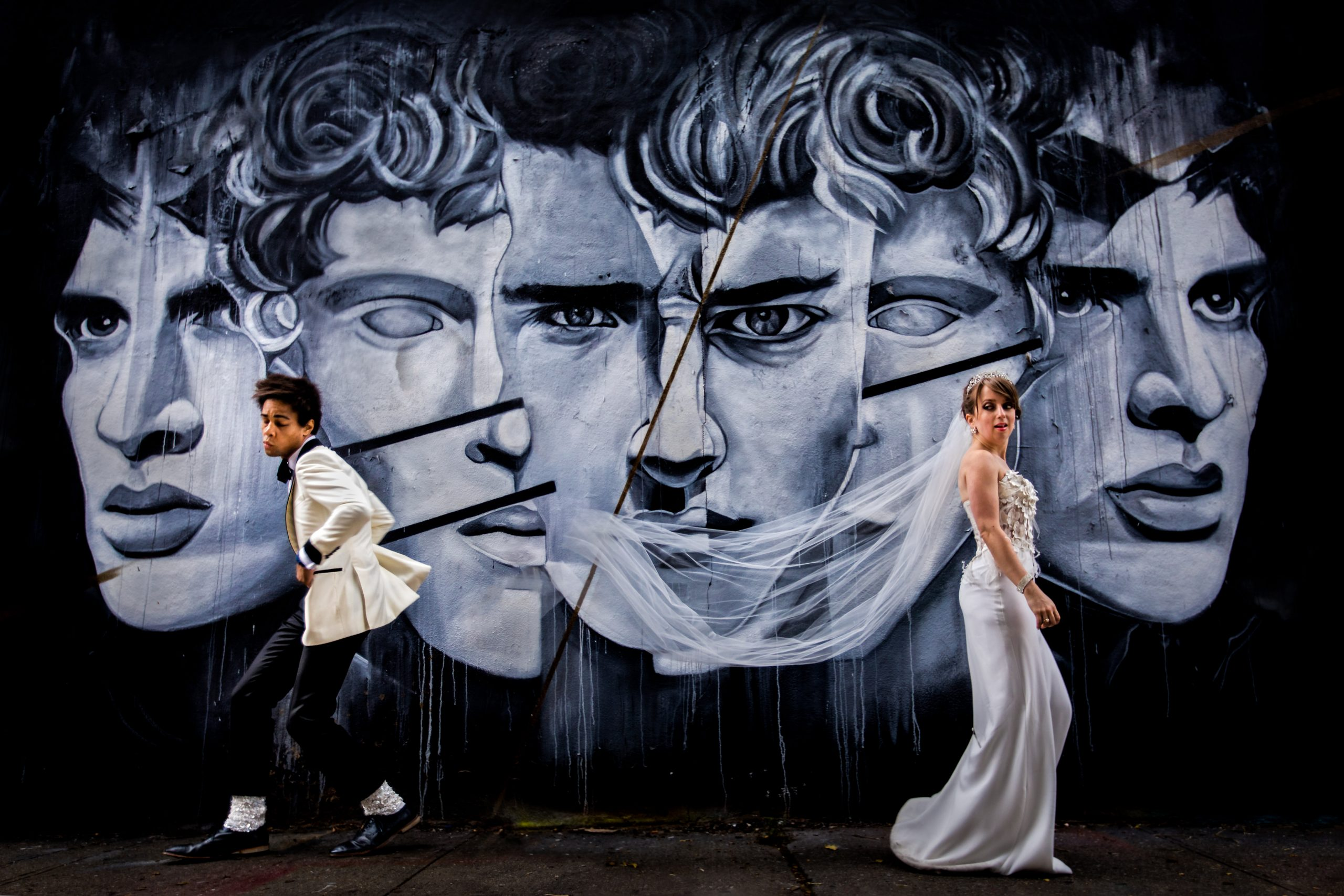 Bride and groom move away from each other in front of a mural