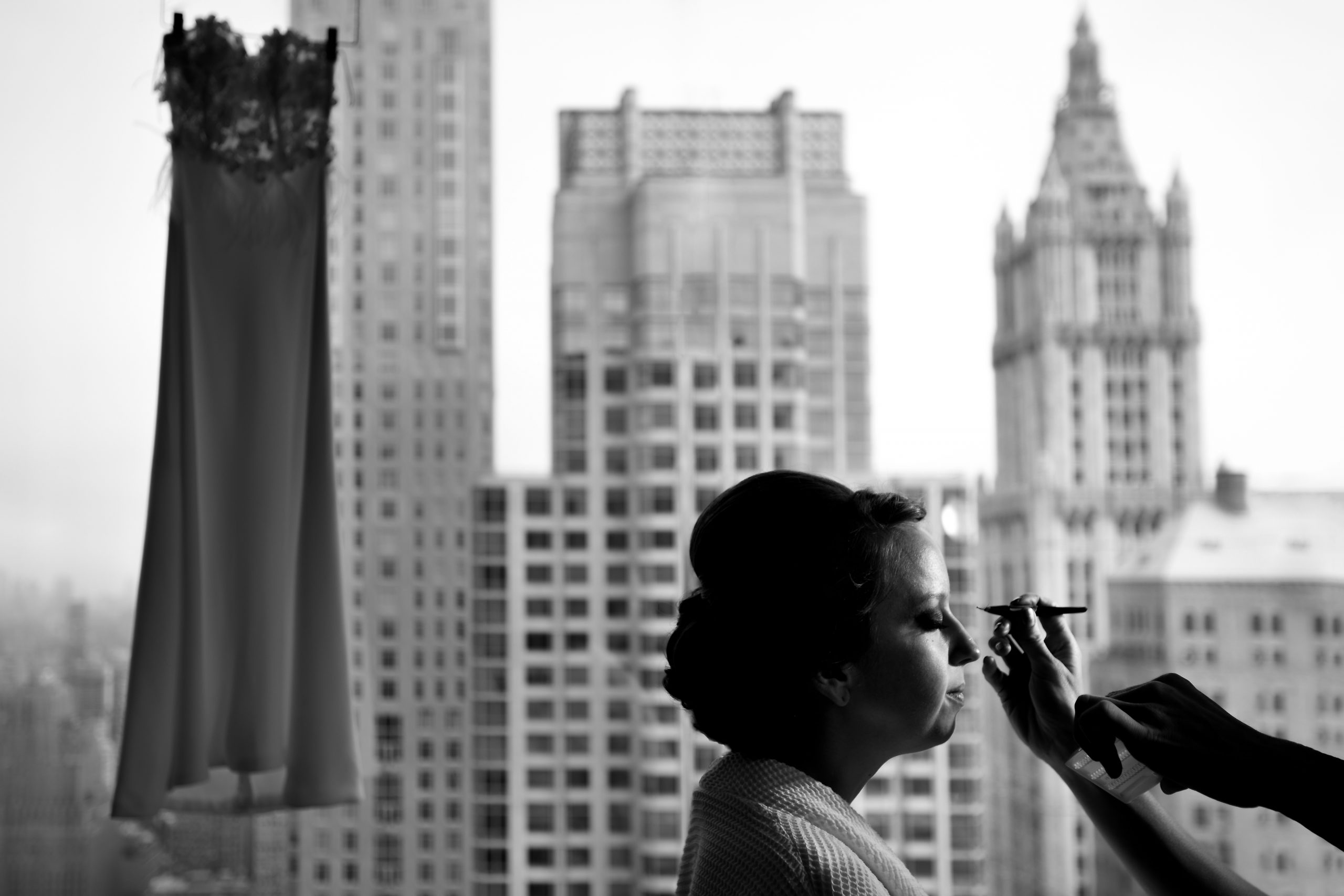 A bride gets her makeup done with a background of high-rise buildings