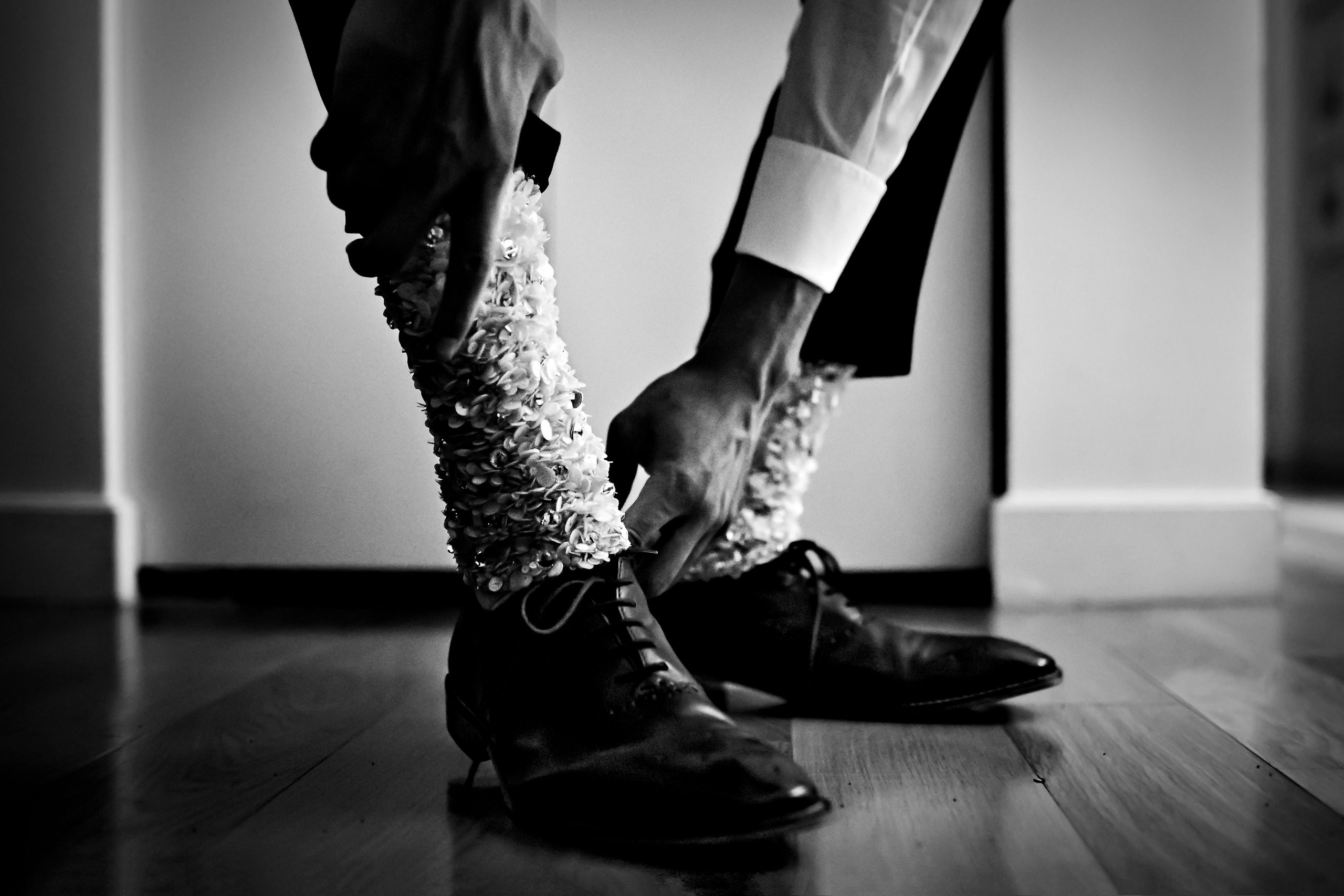 A groom adjusts his dress shoes and sparkling socks