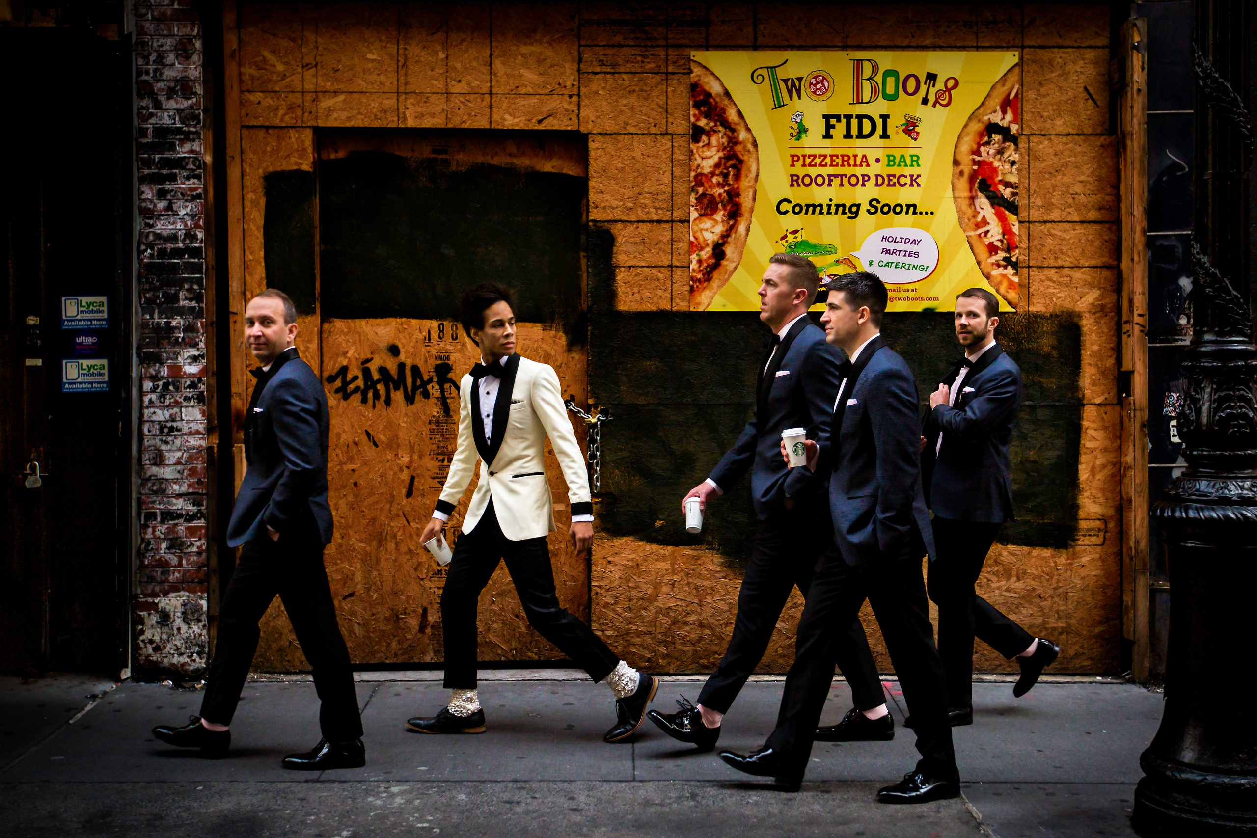 A groom and his groomsmen walking through the streets of New York