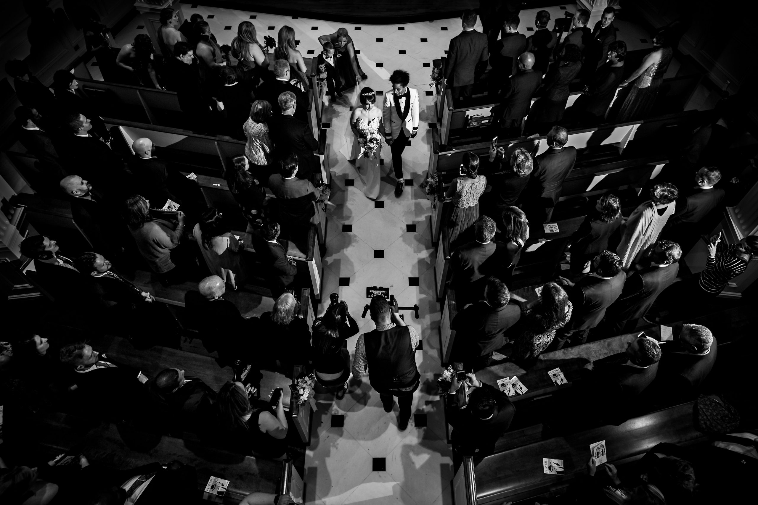 Bird's eye view of bride and groom walking down the aisle