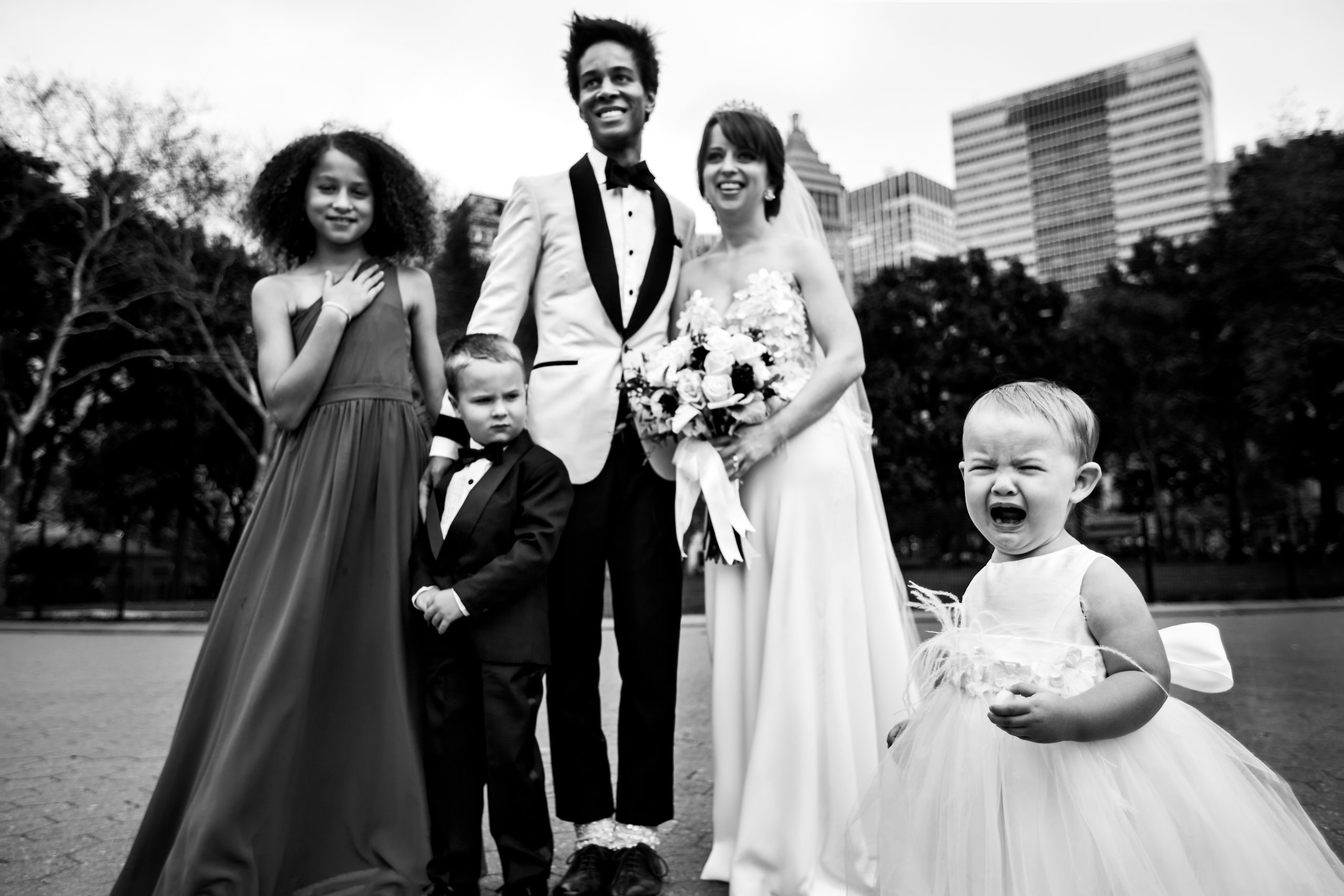 Newlyweds and kids pose for picture while a young girl cries