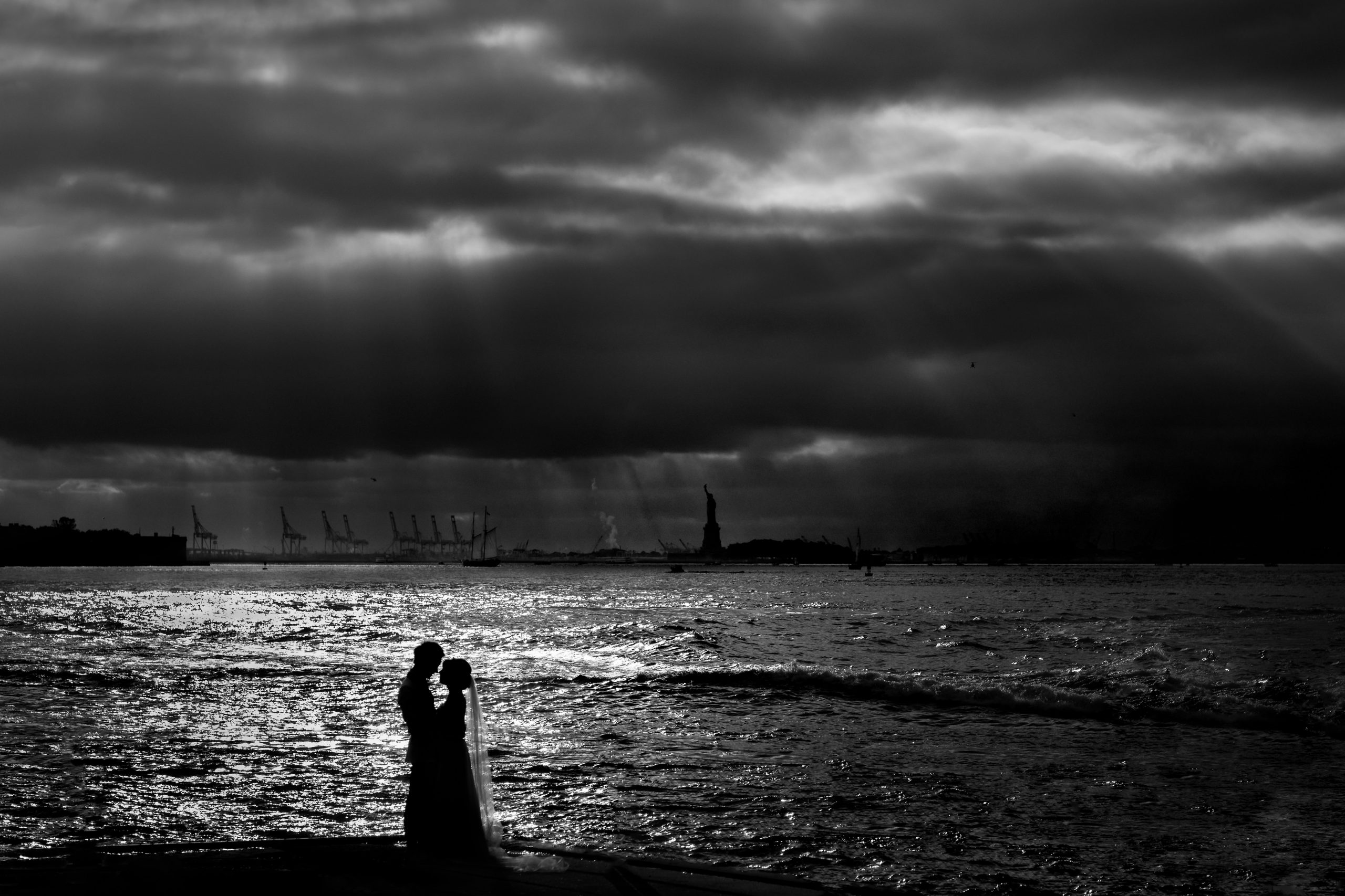 Newlyweds embrace at New York Harbor in front of brewing storm