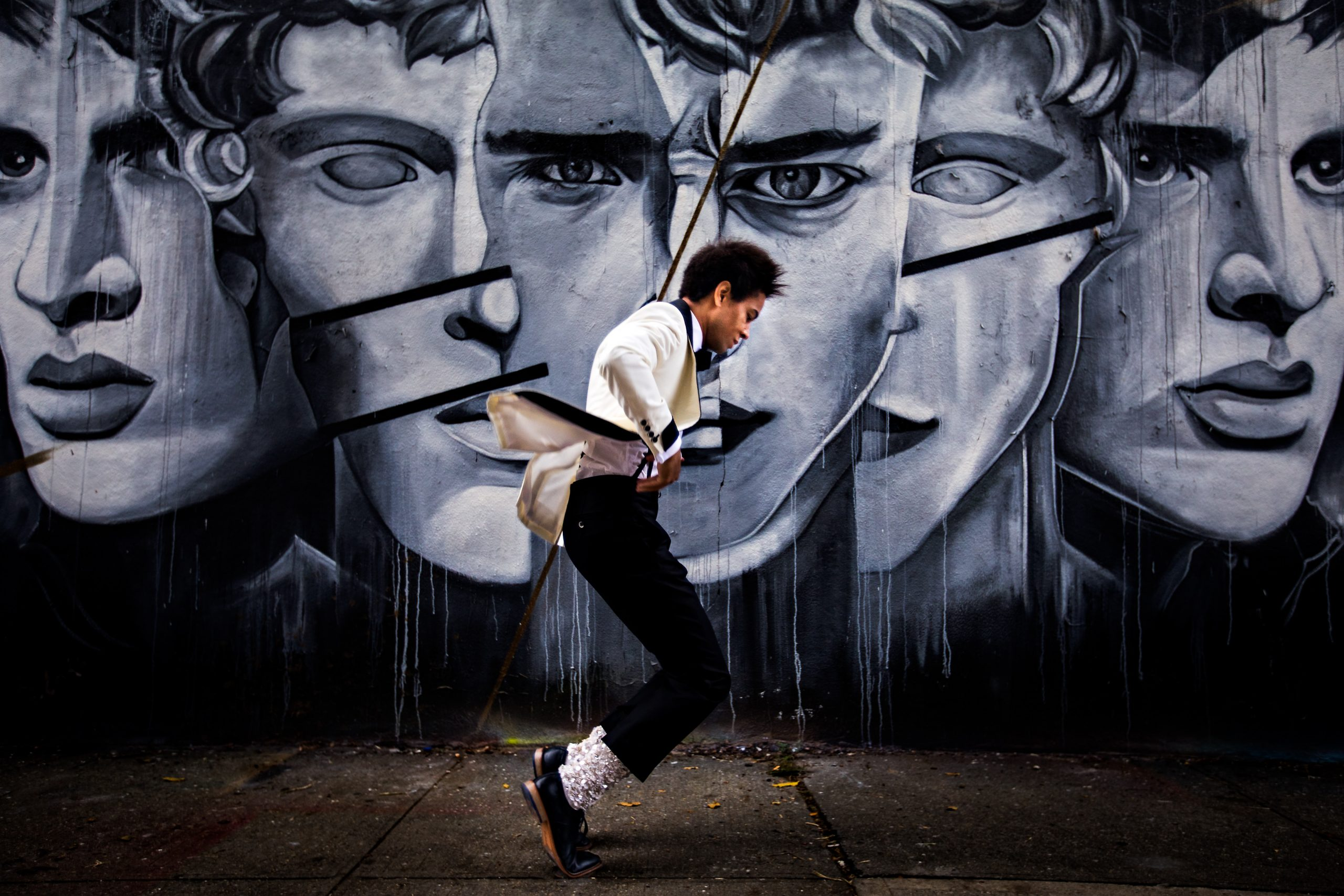 A groom dances in front of a mural of faces