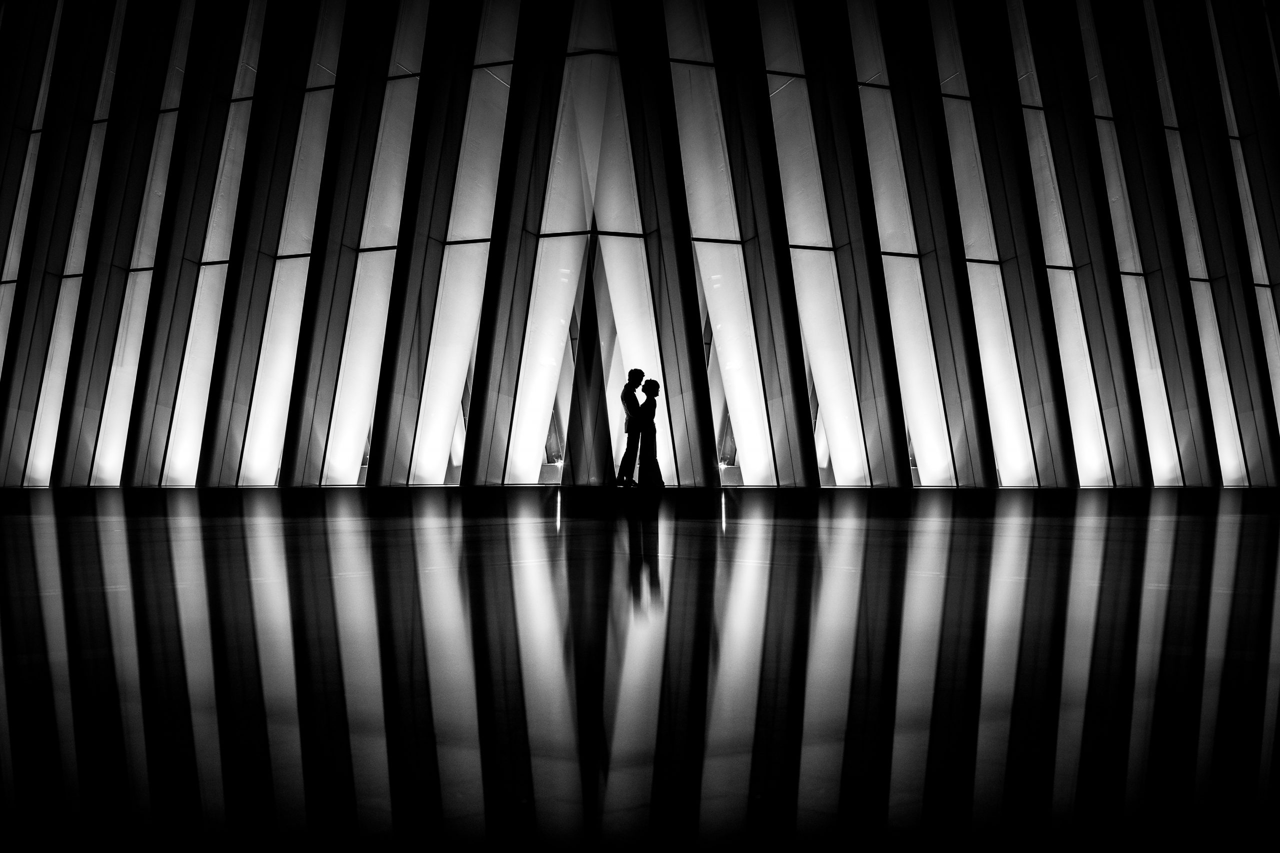 Silhouette of bride and groom embracing in front of glass panel building