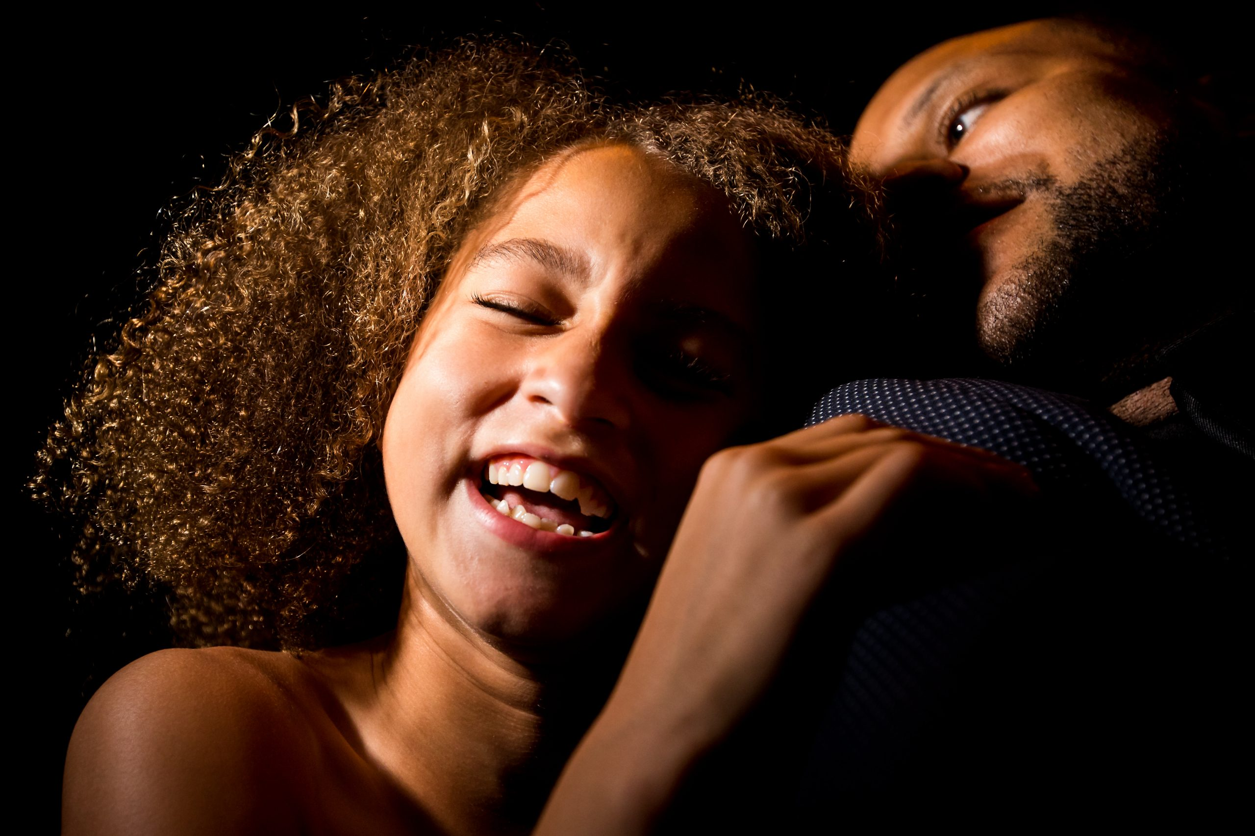 A laughing girl rests her head on a guest's shoulder