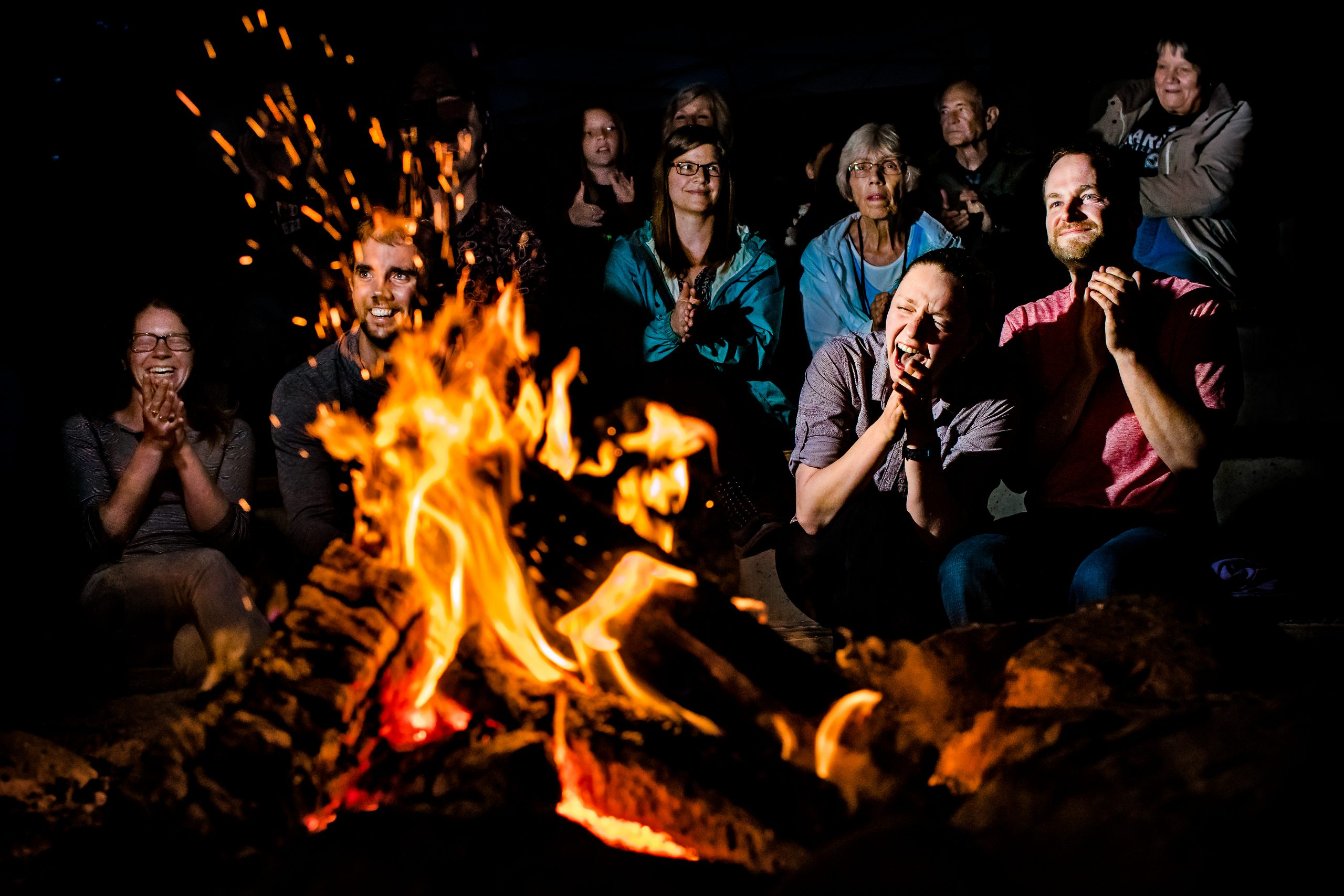 People gather around campfire in high spirits