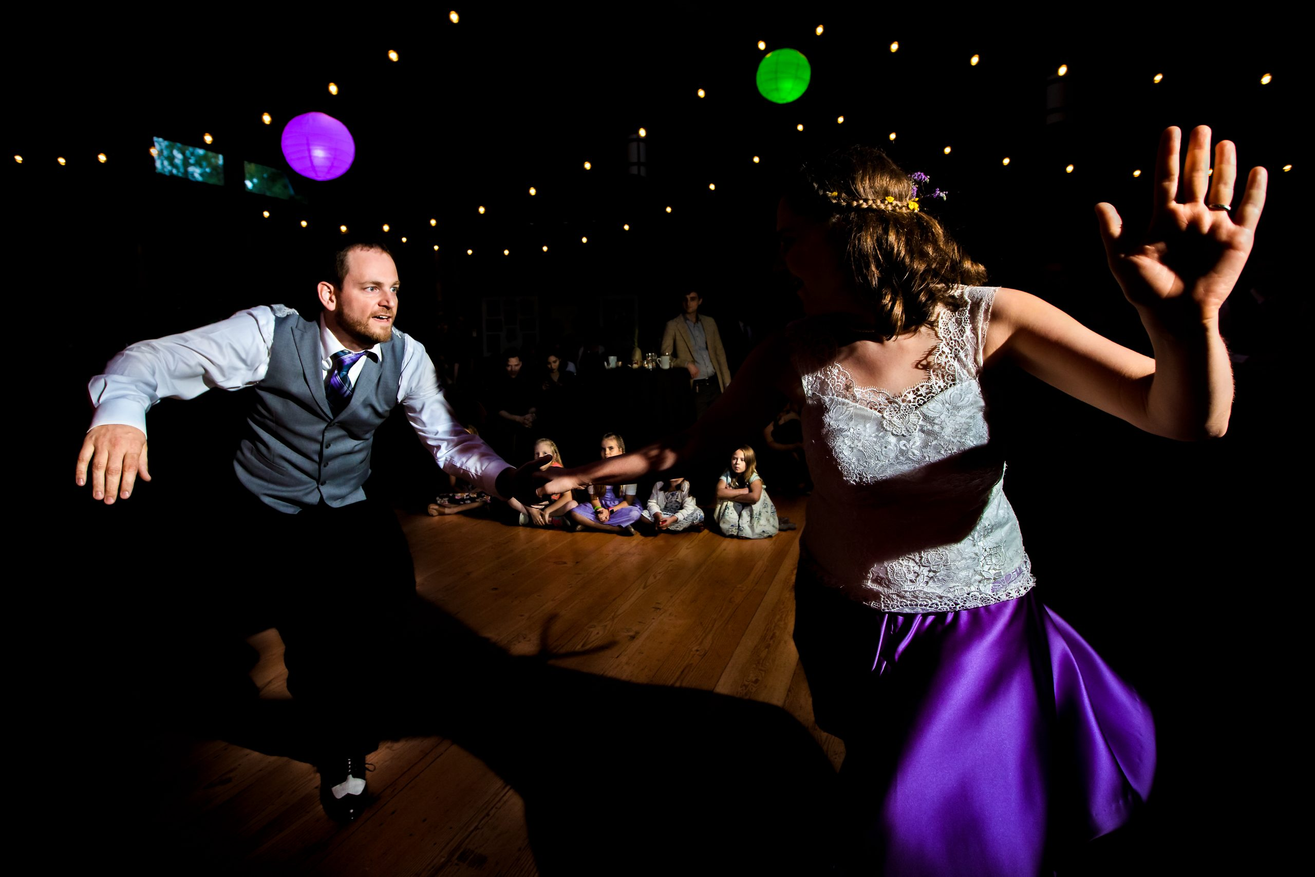 A newly wed couple dance together as people watch