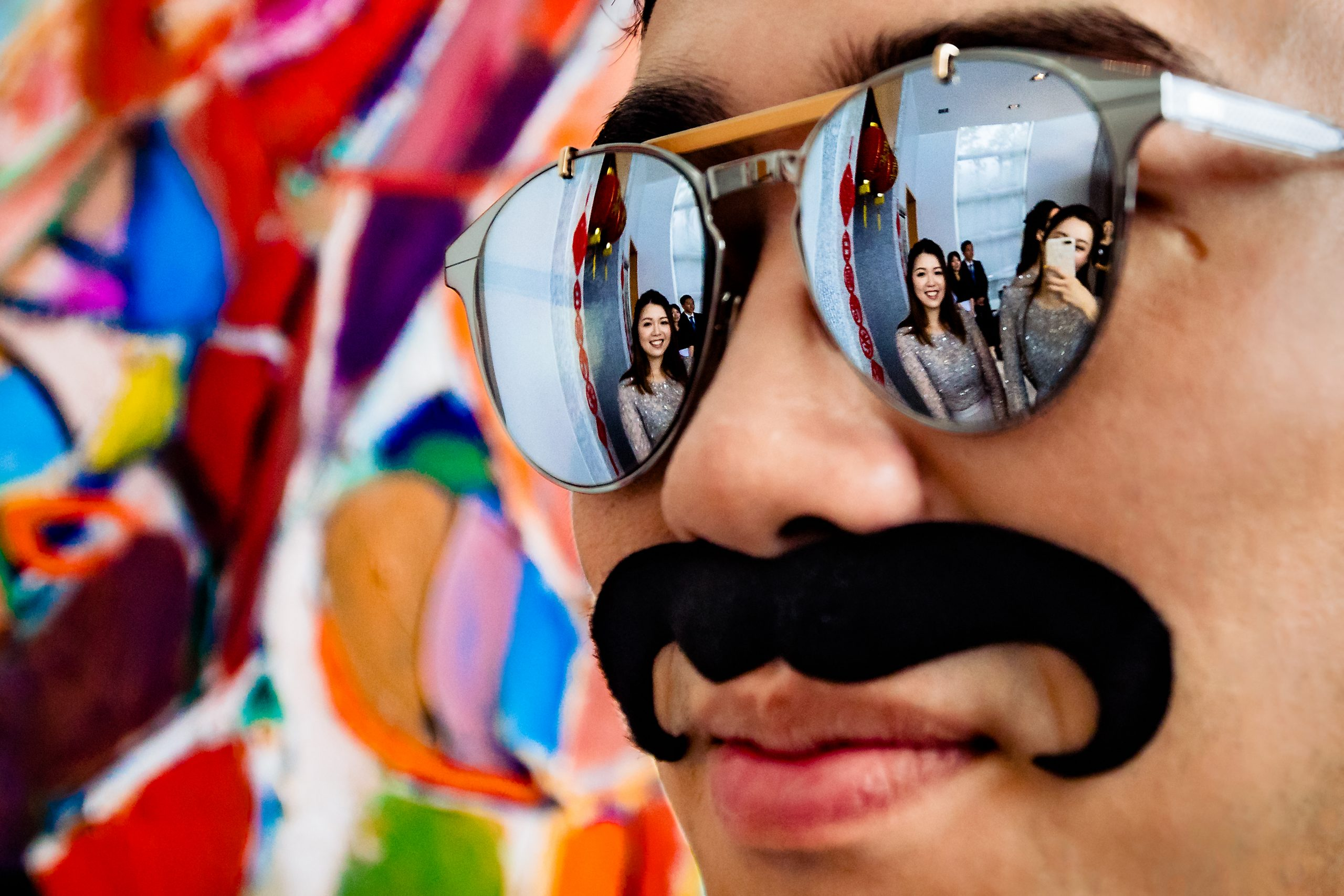 Reflection of bridesmaids is seen in sunglasses of man wearing a fake mustache