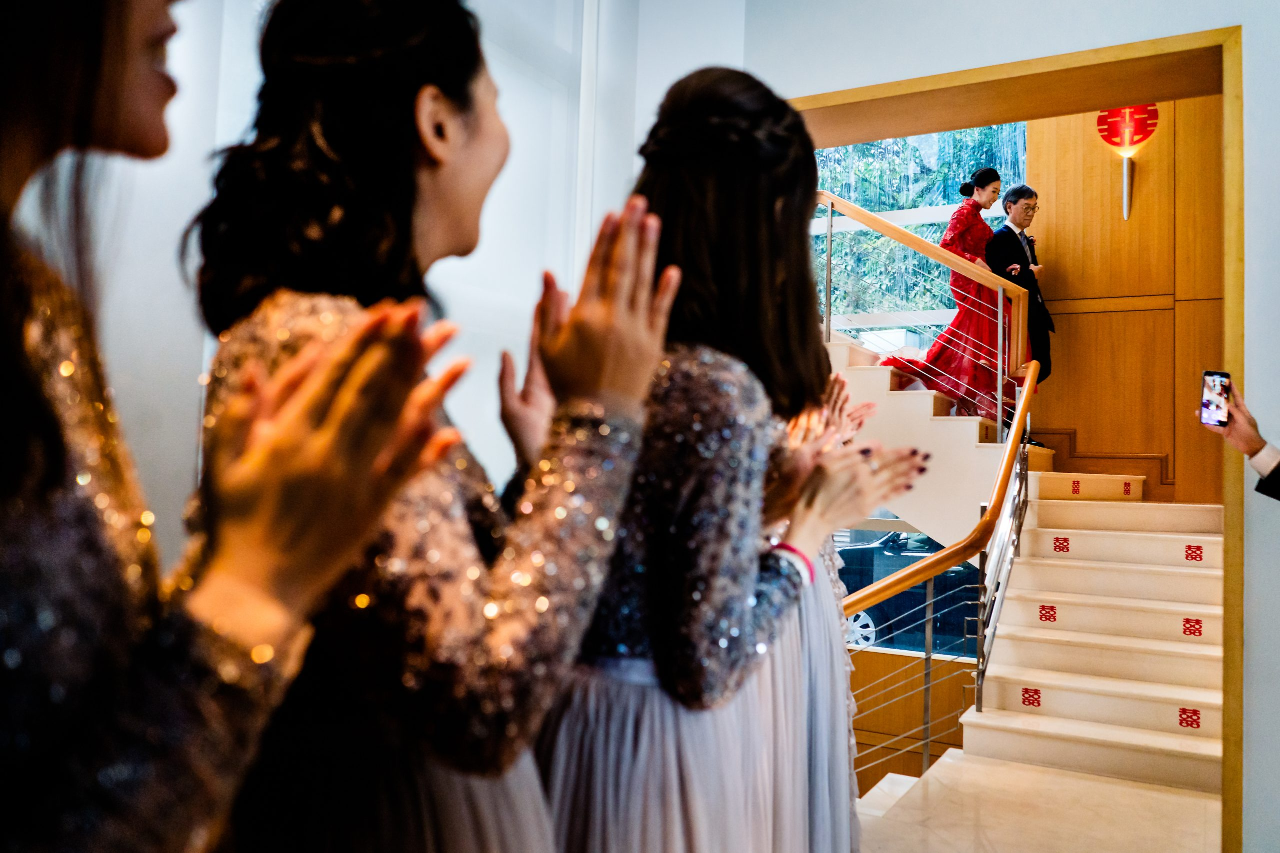 Bridesmaids clap and cheer as bride is walked down a staircase by her father