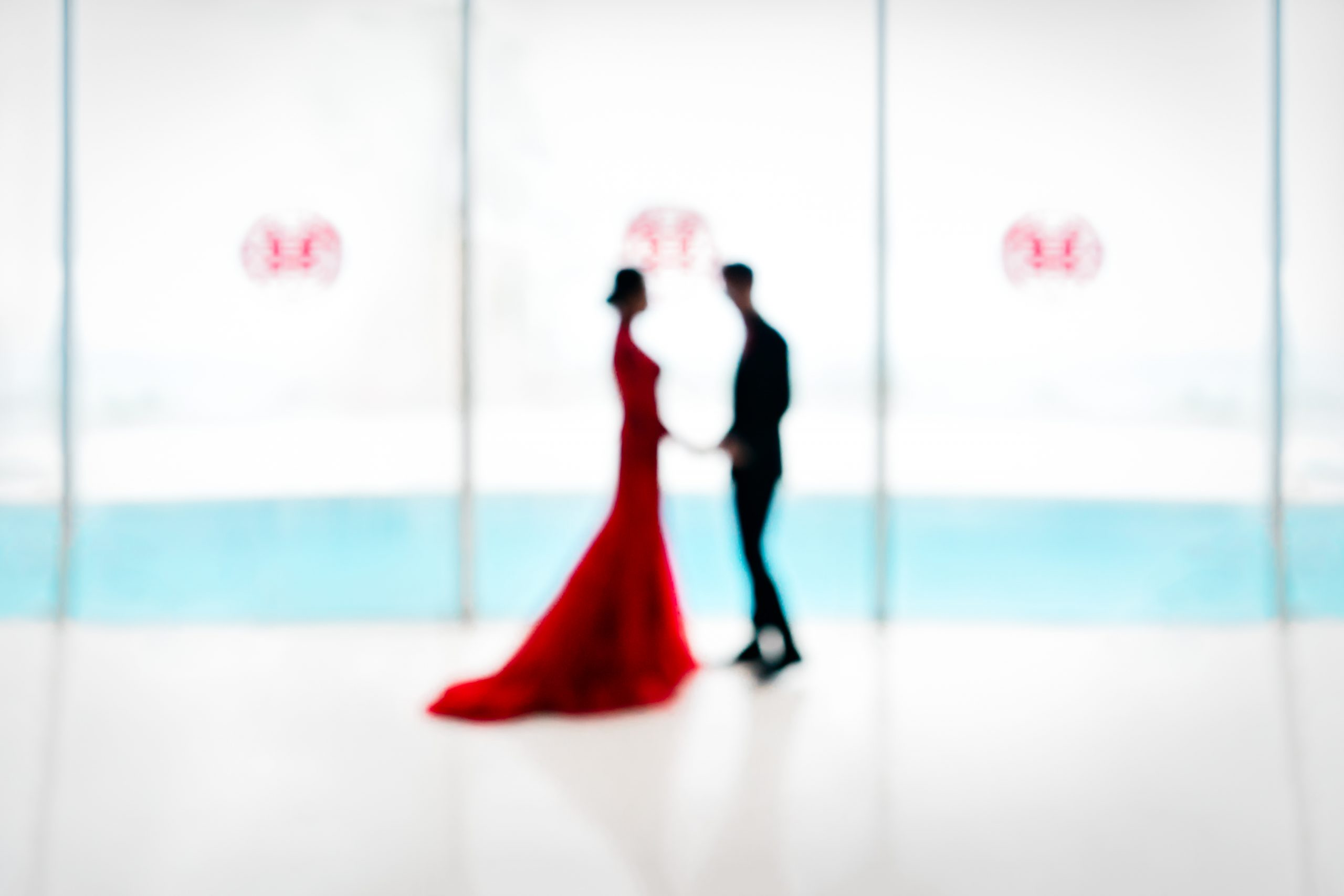 Bride in red and groom in black look at each other holding hands