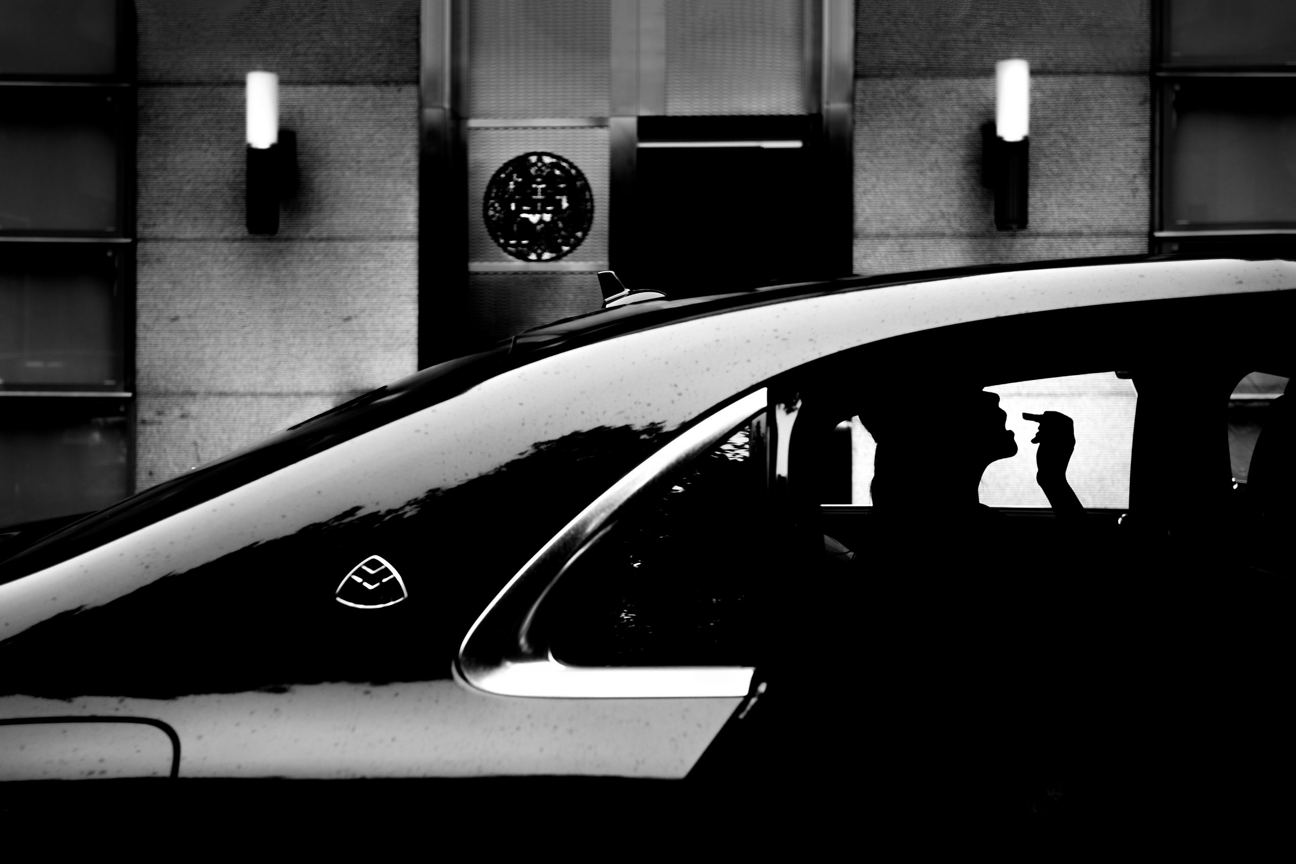 Silhouette of women applying makeup in a car
