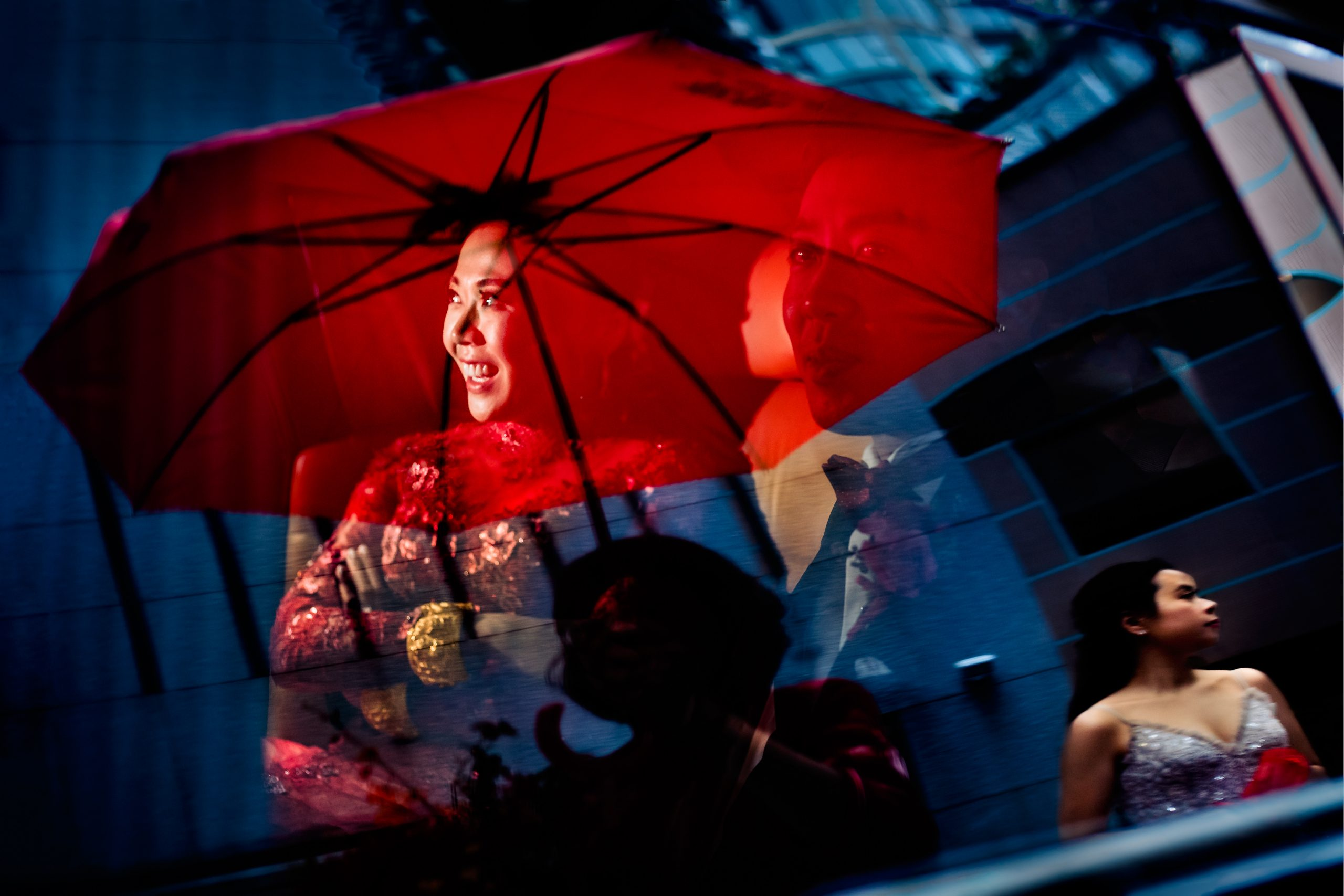 Bride and groom sit together in car with reflection of a red umbrella