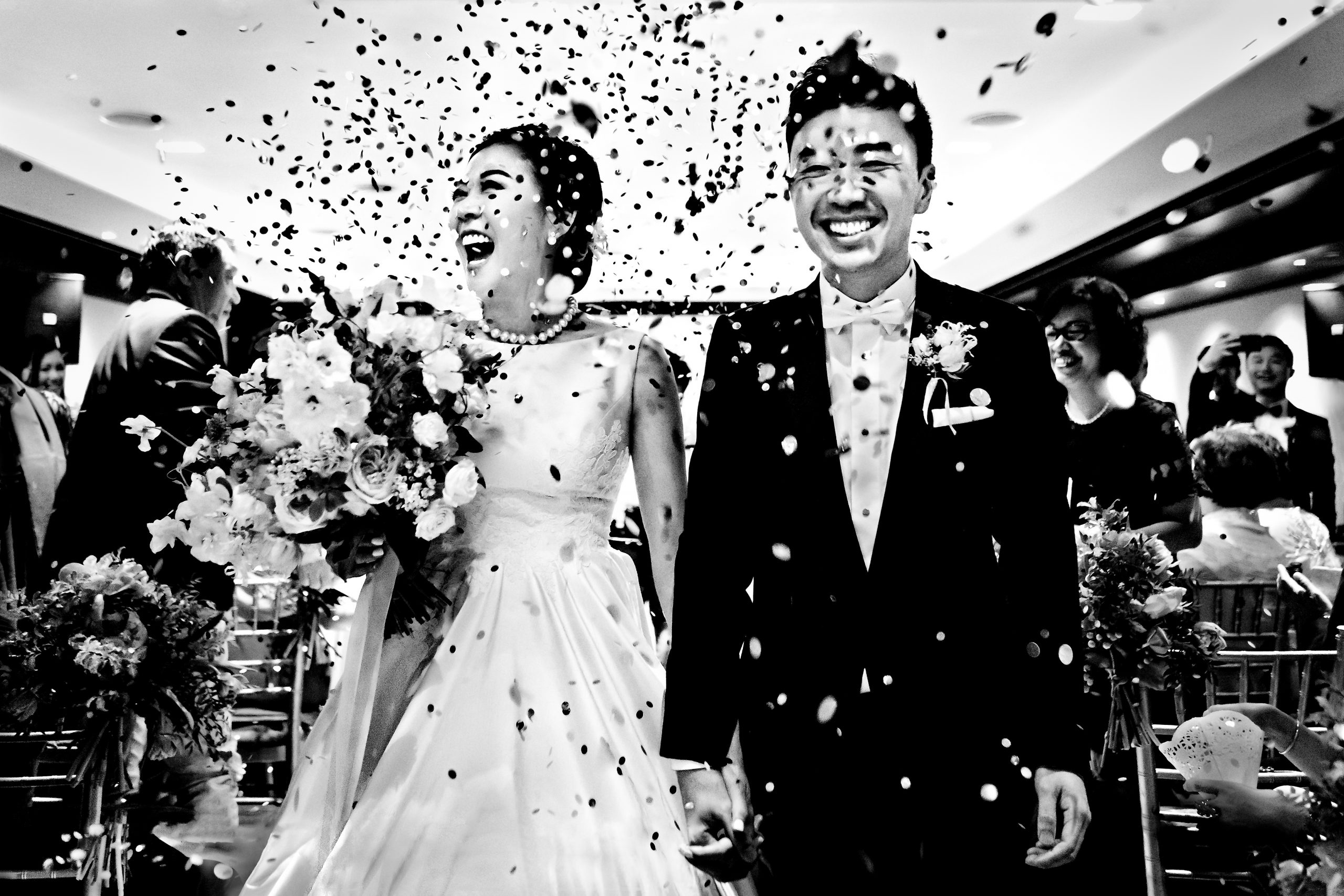 Bride and groom walk down aisle holding hands as confetti showers them from above
