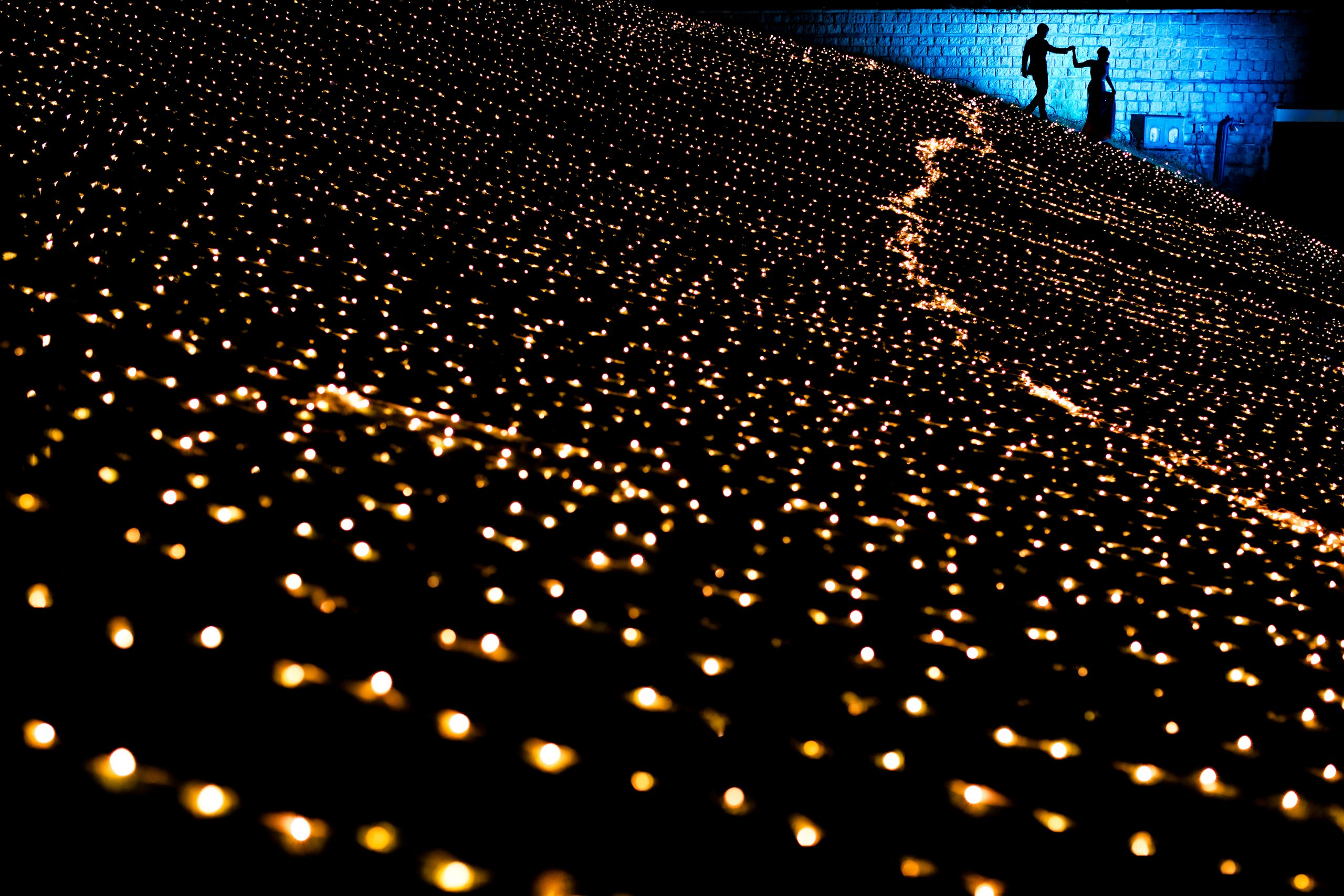 Silhouettes of bride and groom walking hand in hand with foreground of sparkling lights on the ground at night