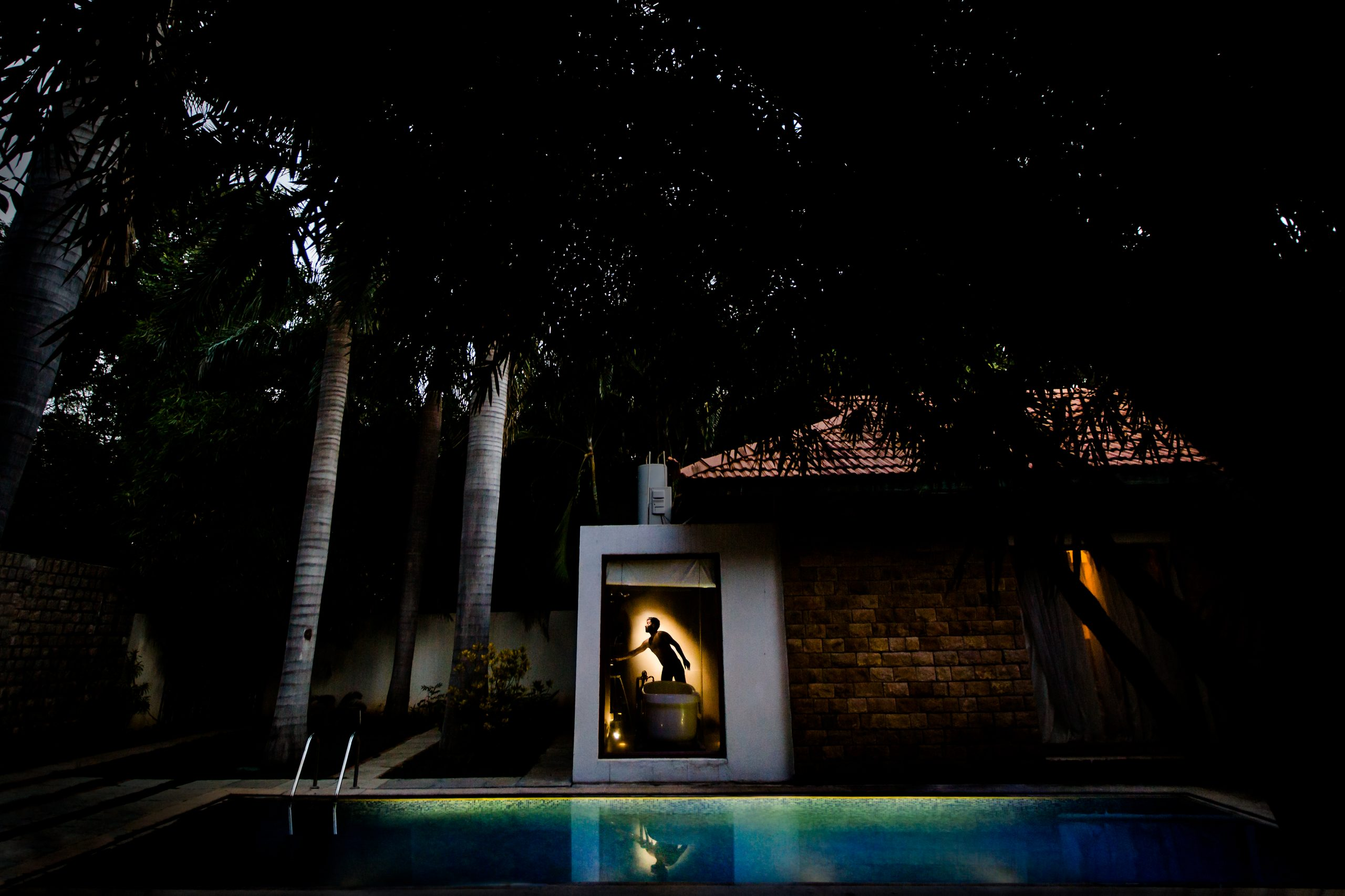 Groom is seen illuminated in the washroom of pool side house