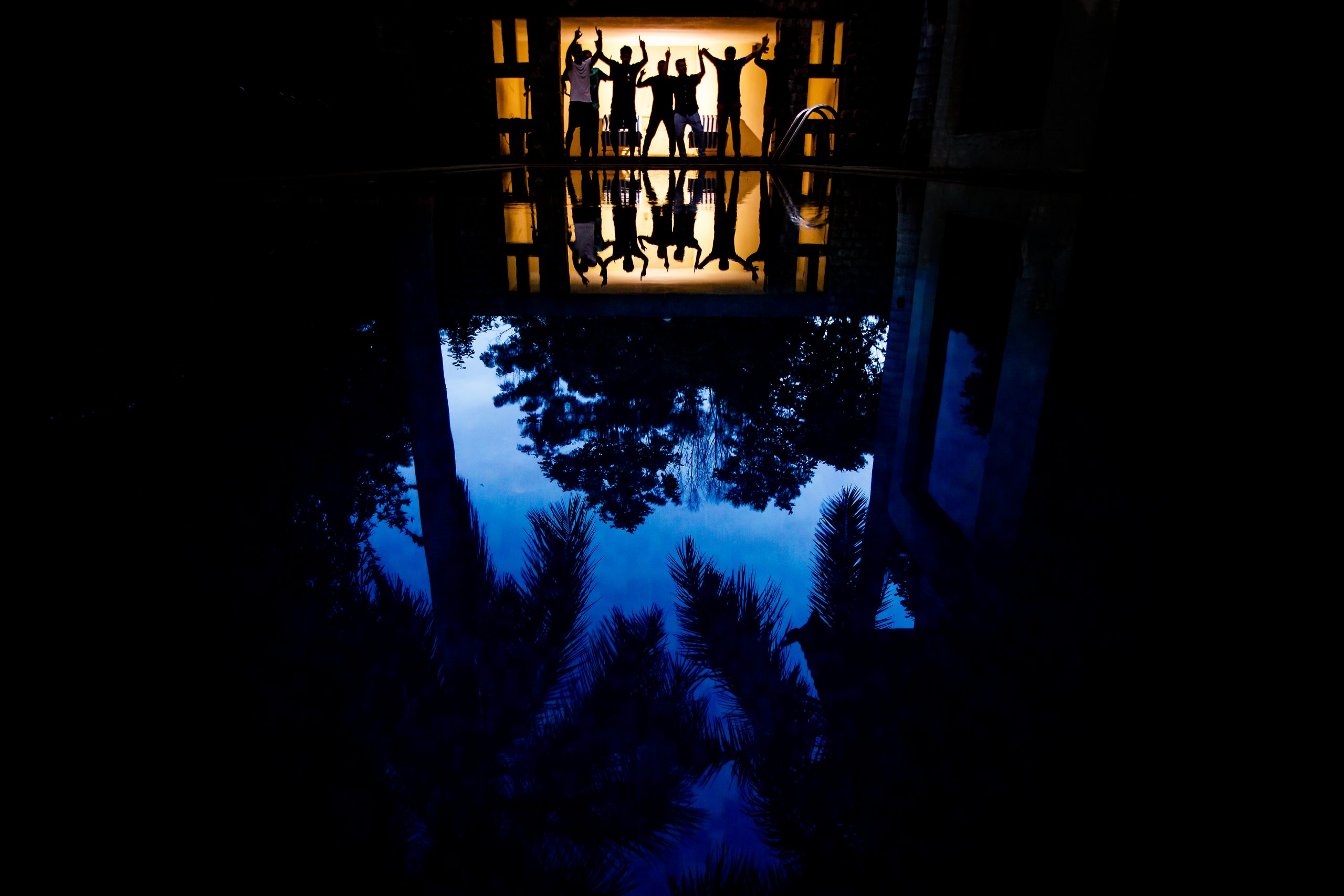 Silhouette of groom and groomsmen dancing in a room with a reflection of themselves and trees on the pool