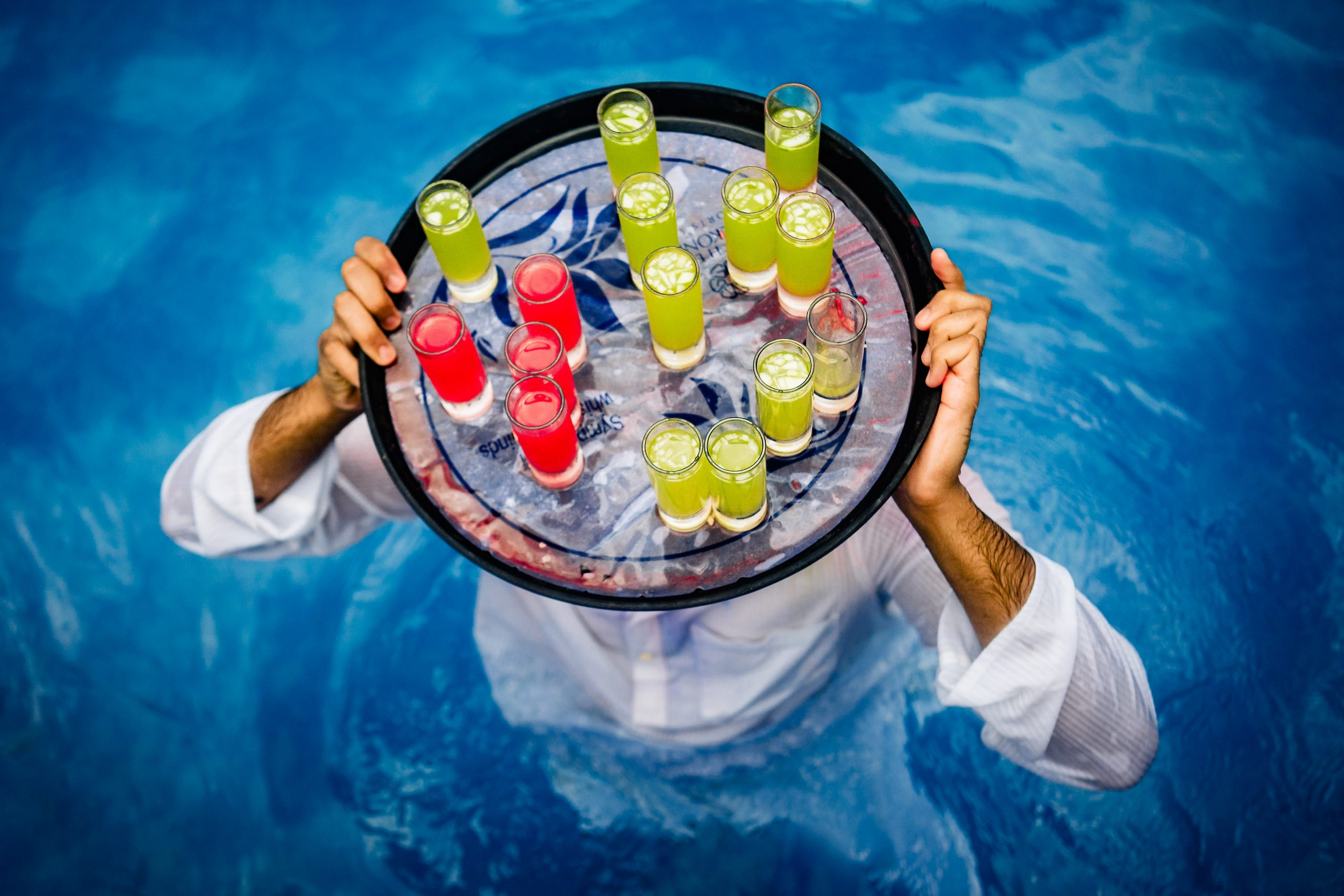A man stands in a pool with a tray of drinks on his head