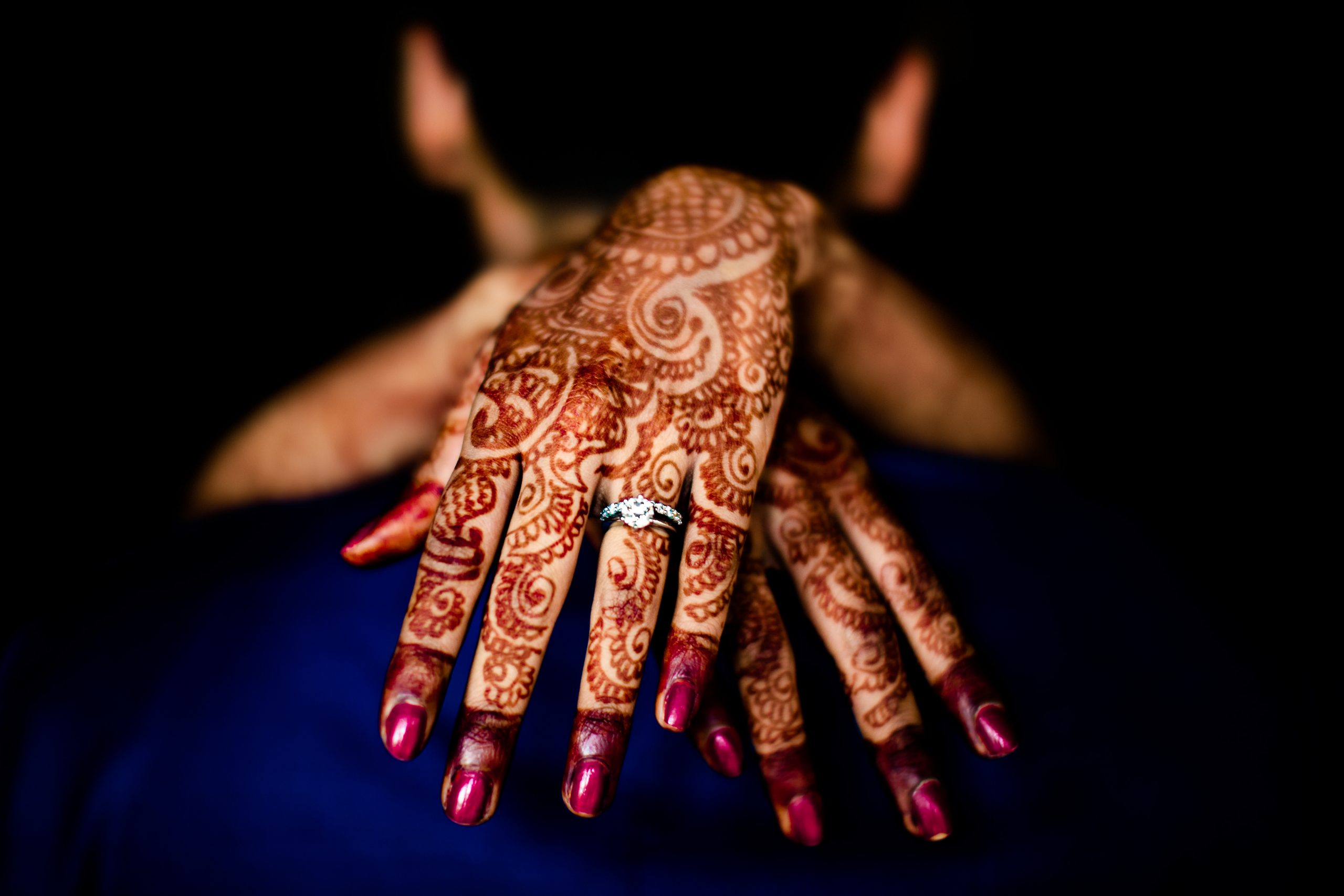 An bride's wedding ring on top of her mehndi hand art