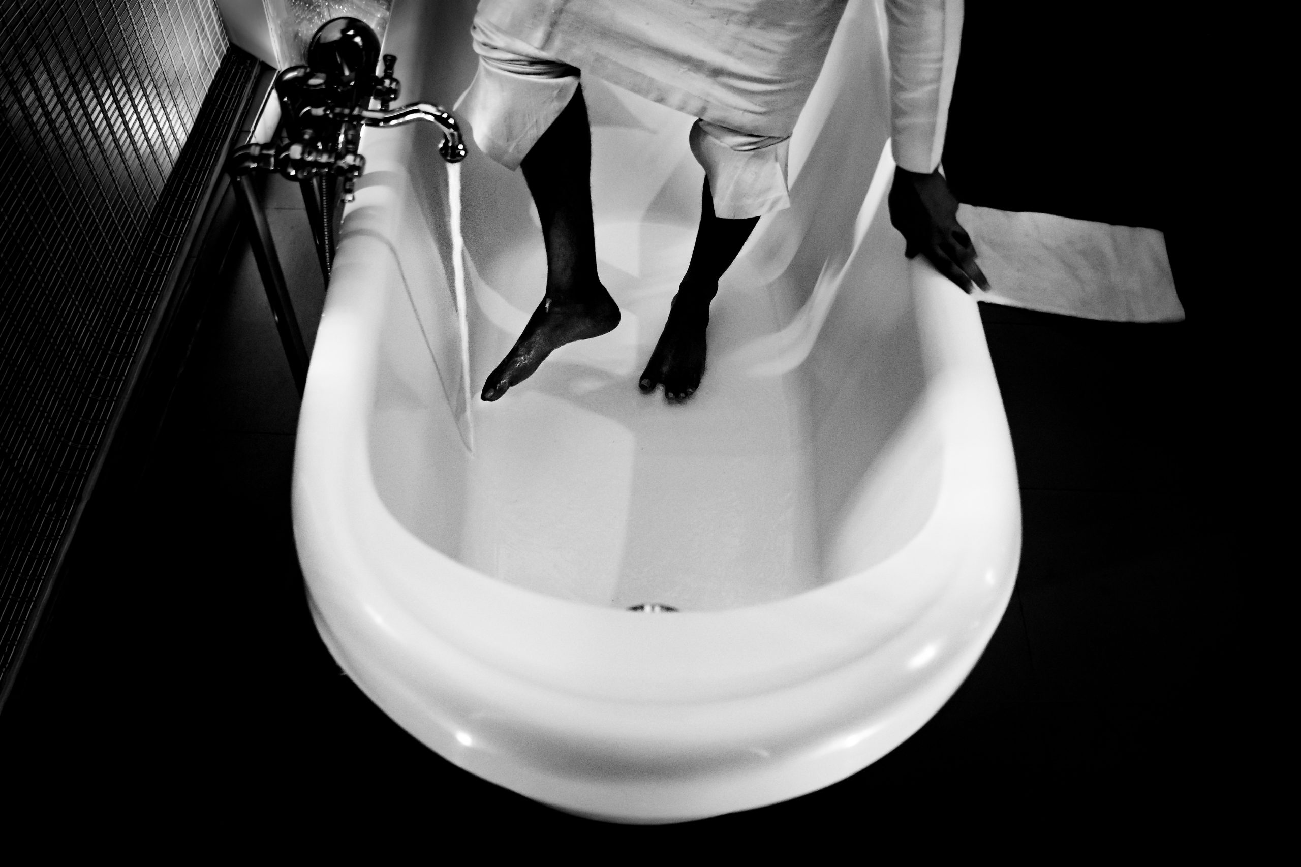A groom washes his feet in the tub