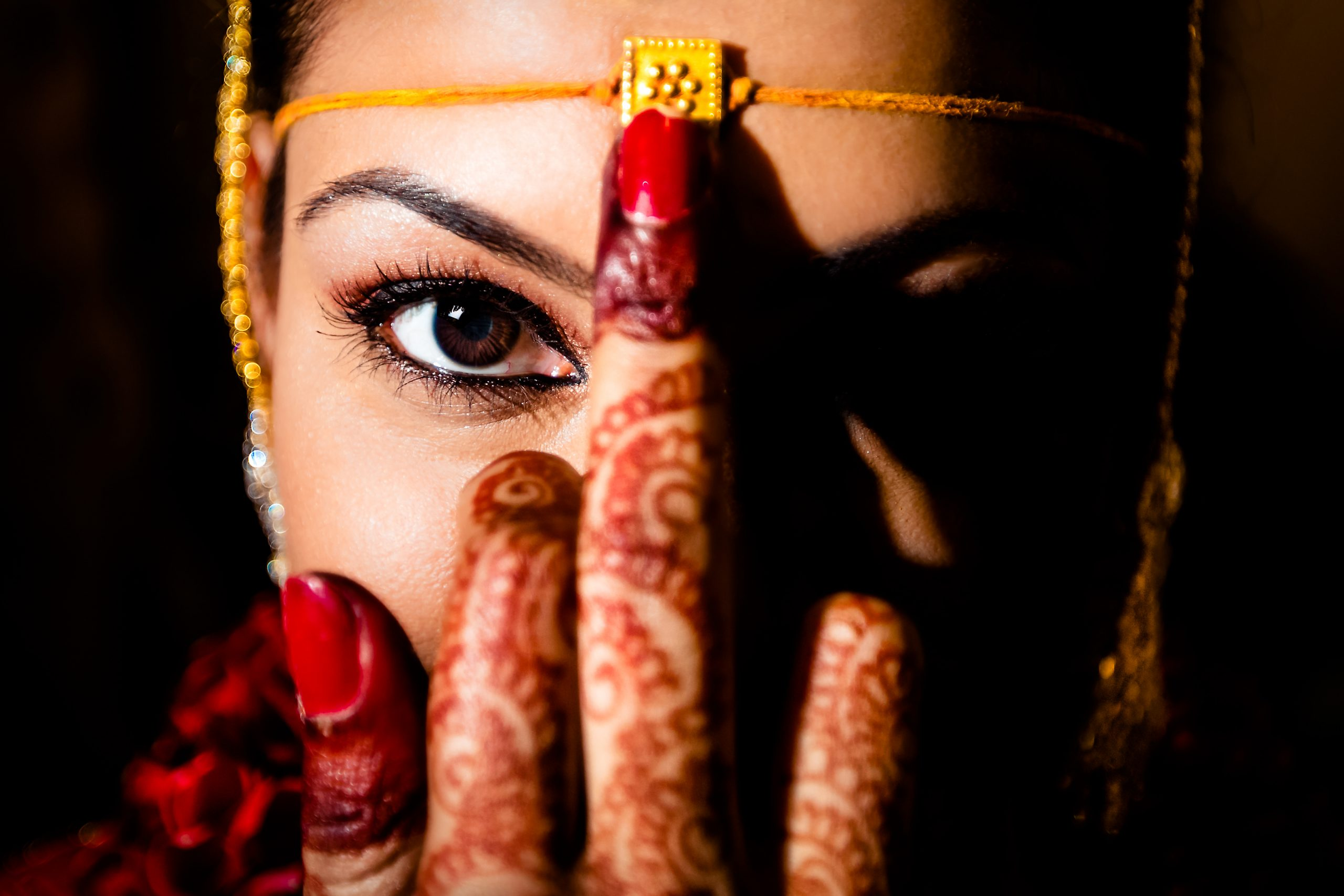 An Indian bride puts her hand on circlet