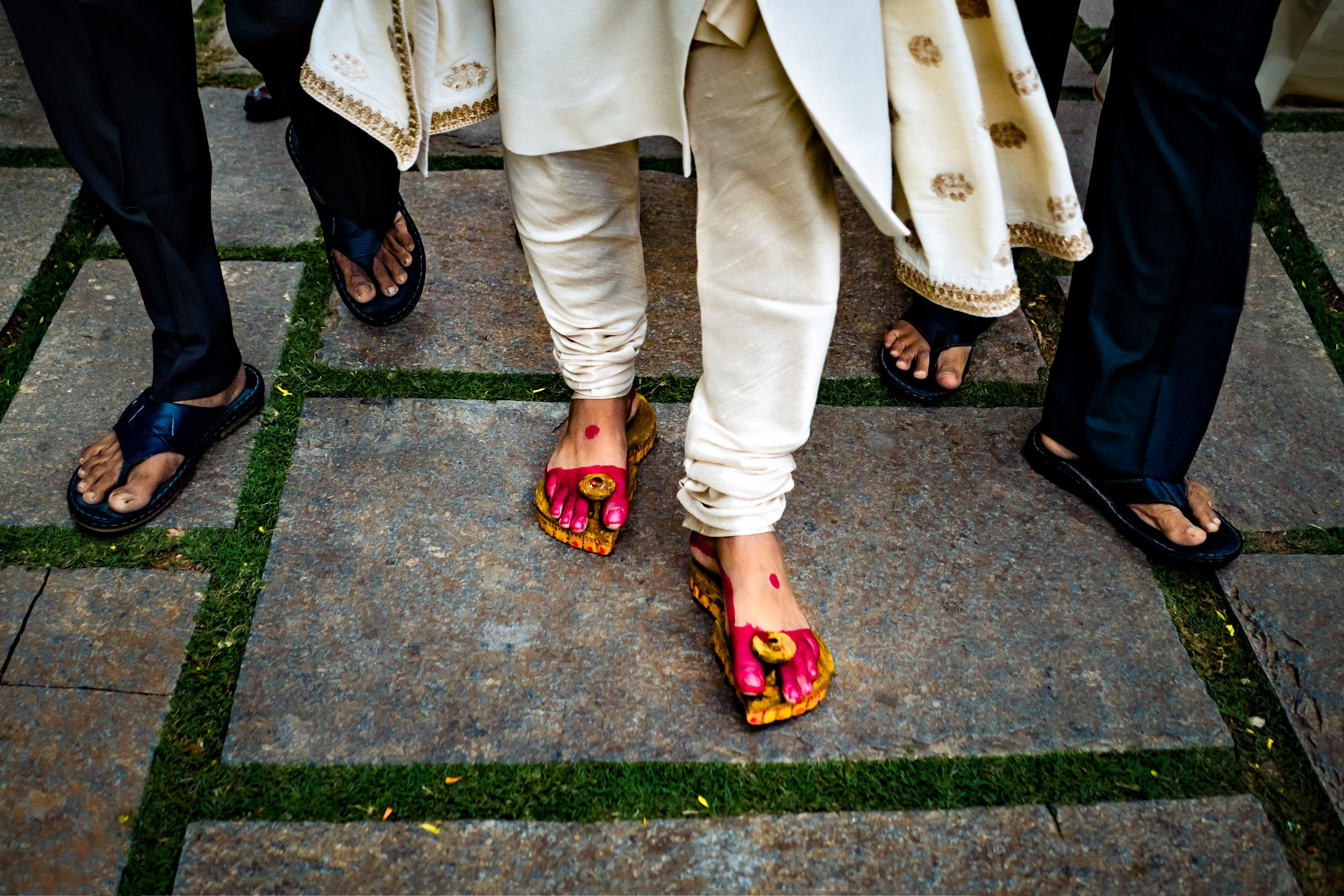 Groom and guests wearing sandals walk across stone path