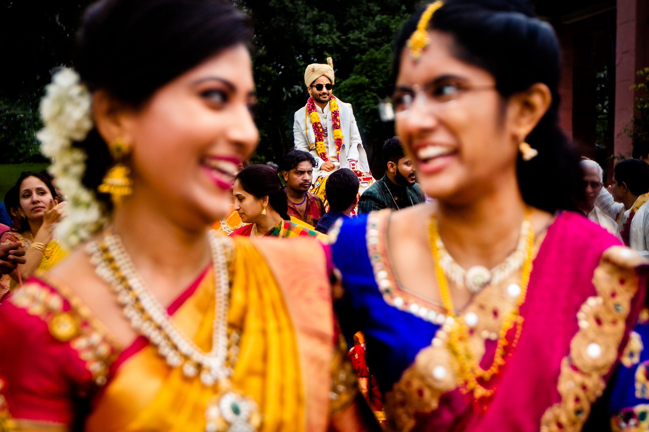 Groom can be seen behind women wearing colorful attire