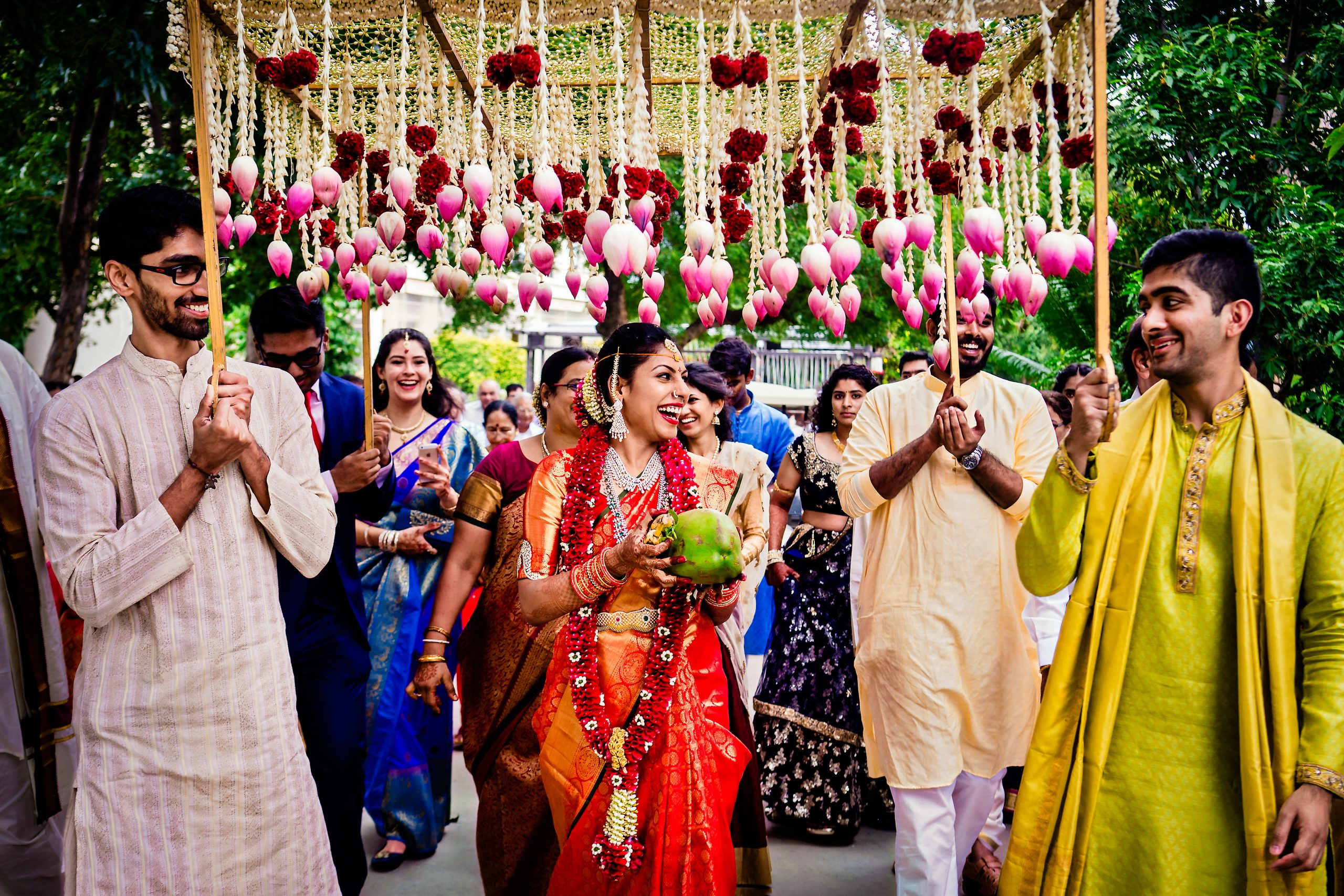 Indian bride walks to the ceremony with bridal party under a floral mandap