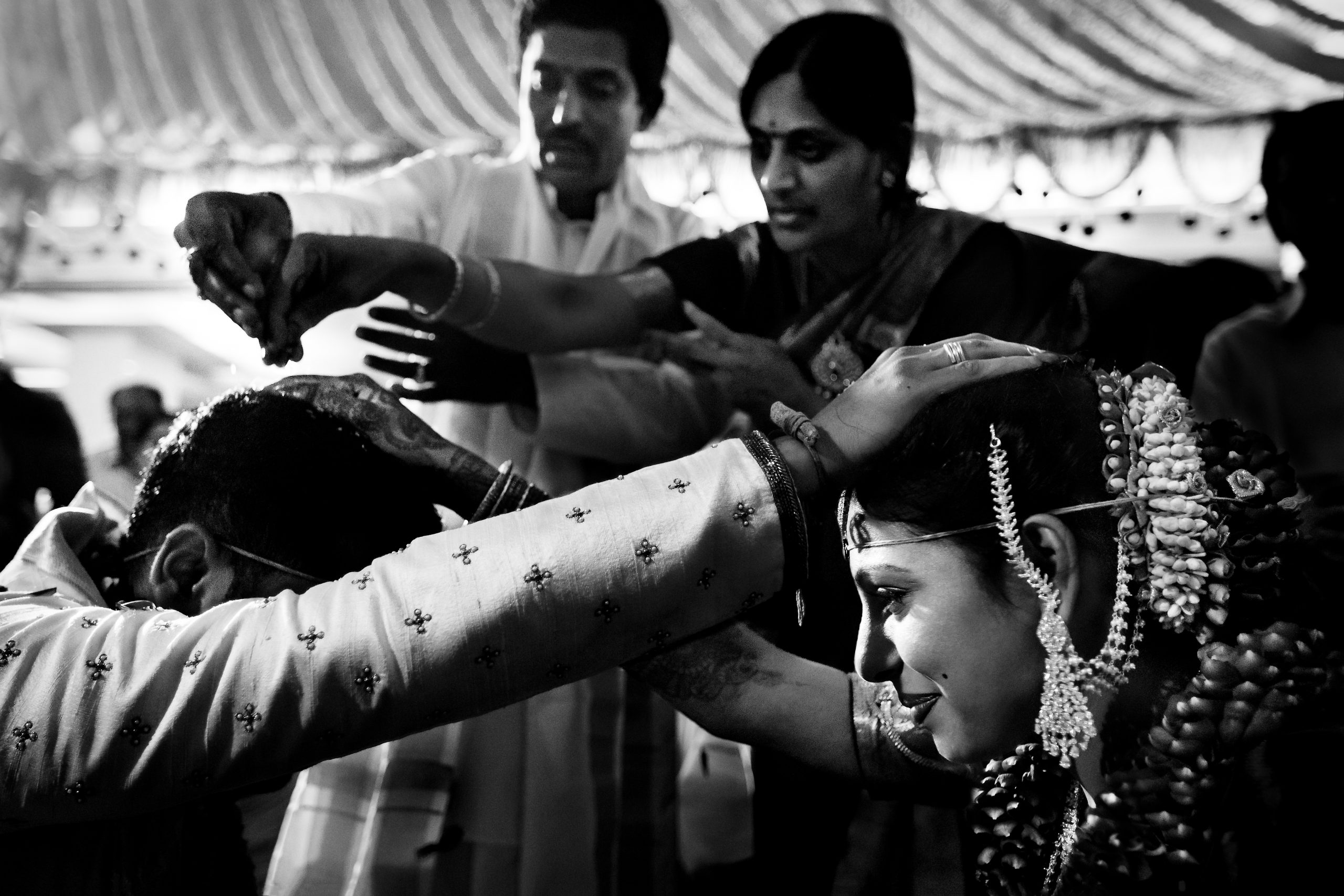 Bride and groom touch each other's heads by one hand at ceremony