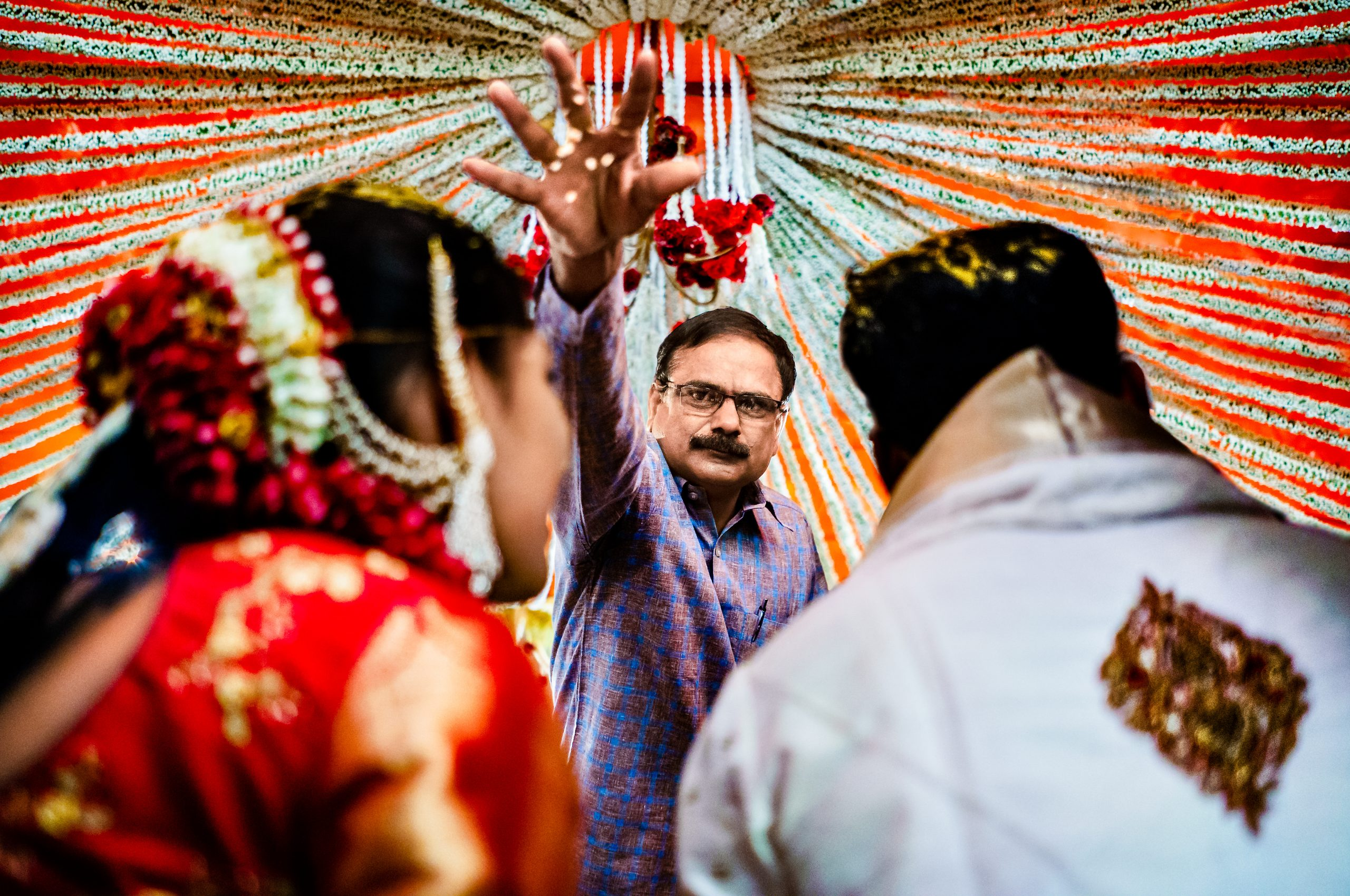 Man sprinkles material on bride and groom during an Indian wedding ceremony