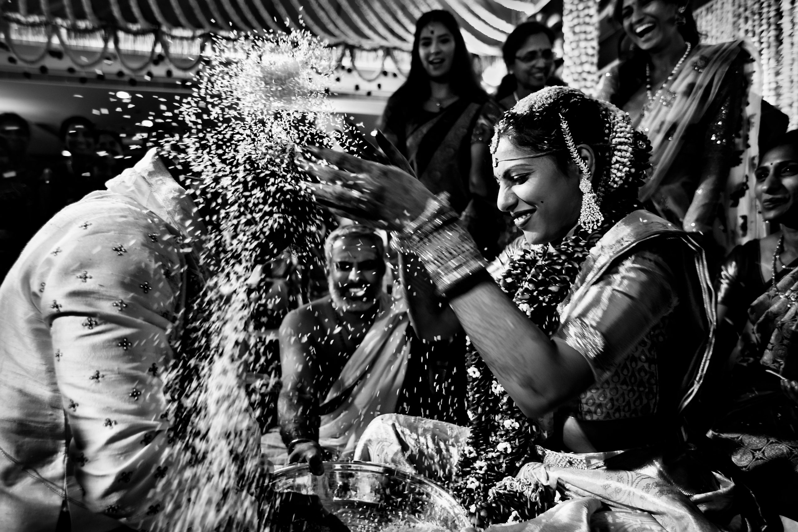 Indian bride pours rice over head of groom