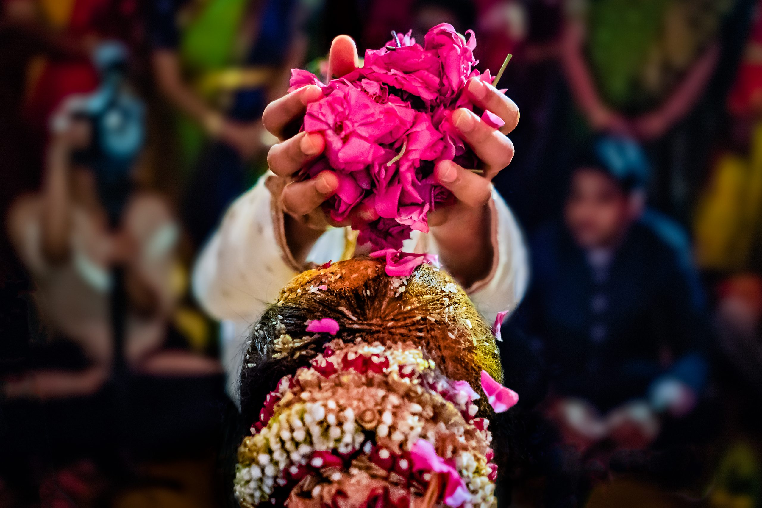 An Indian groom places flower petals on bride's head at wedding ceremony