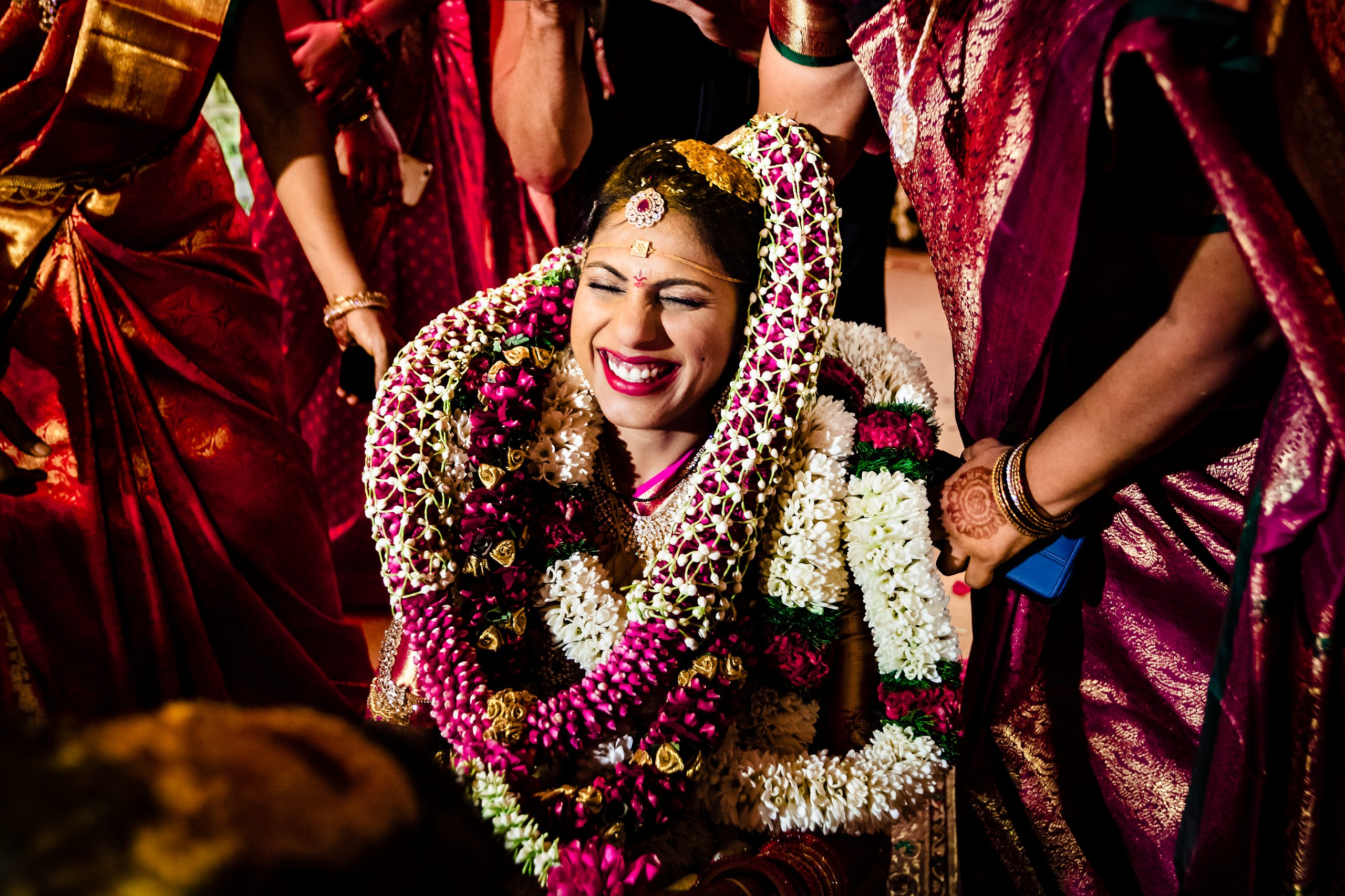 Smiling Indian bride with many colorful garlands