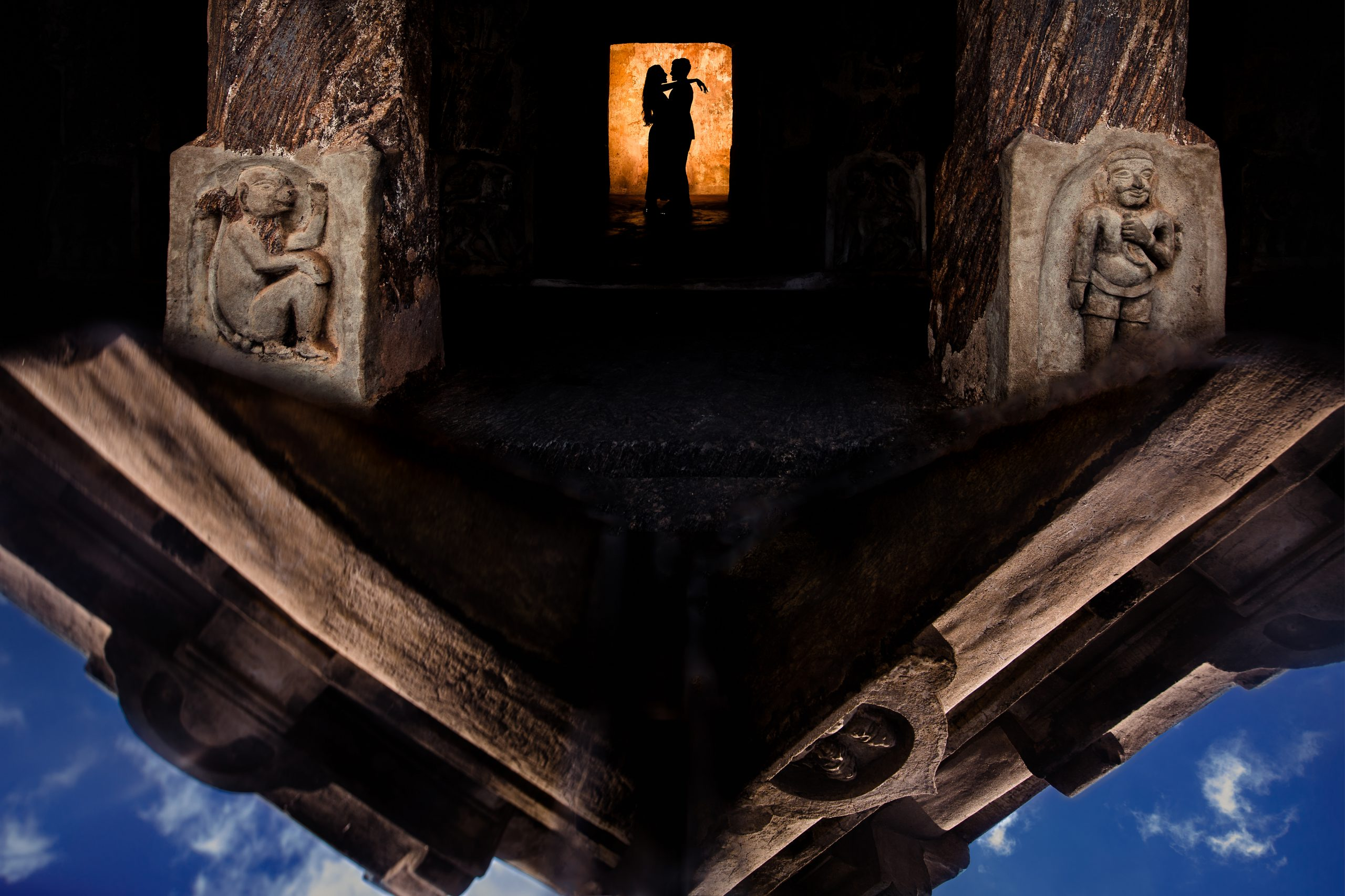 Silhouette of groom and bride embracing in an ancient Indian temple