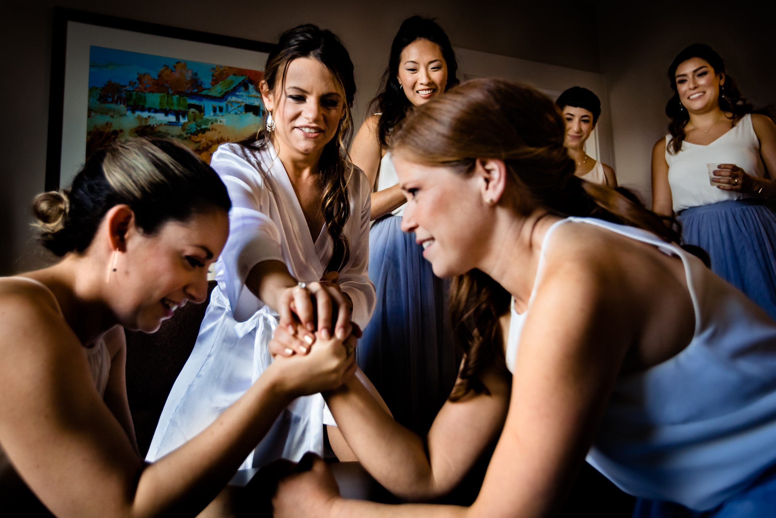 Bride officiates arm wrestling between bridesmaids