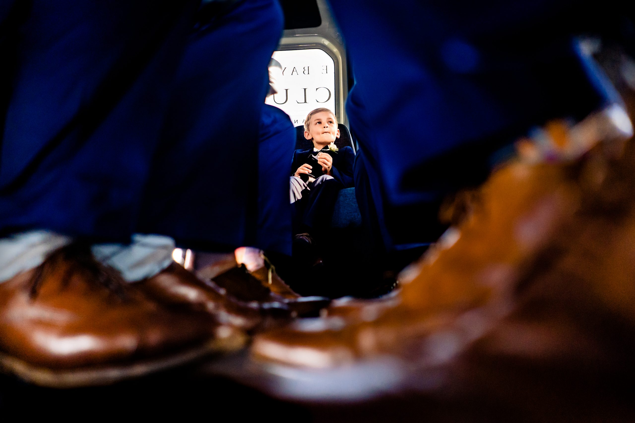 Through a column of the dress shoes of the groomsmen a young boy can be seen in formal attire