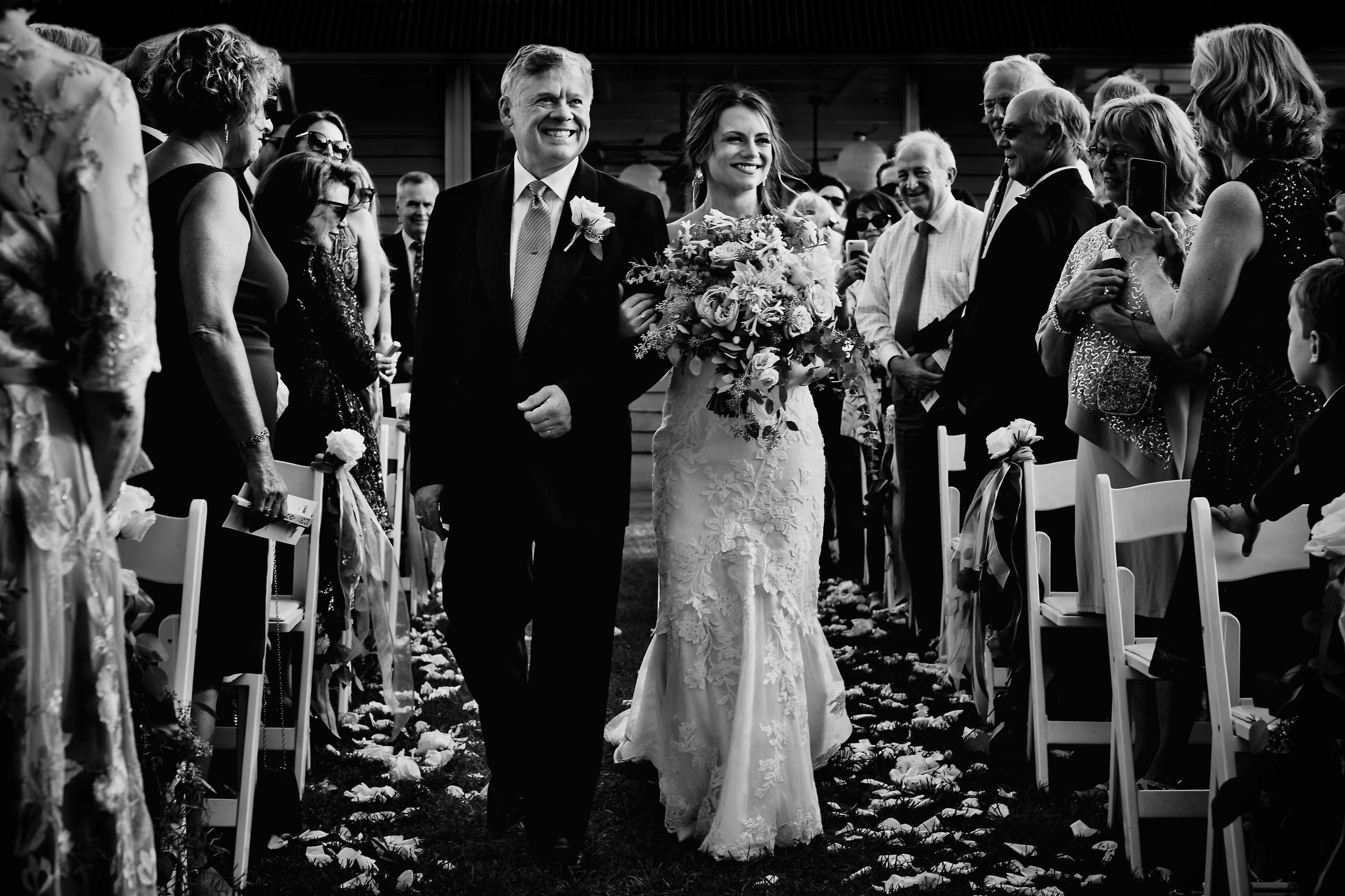 Weddings guests stand as the bride's father walks her down the aisle