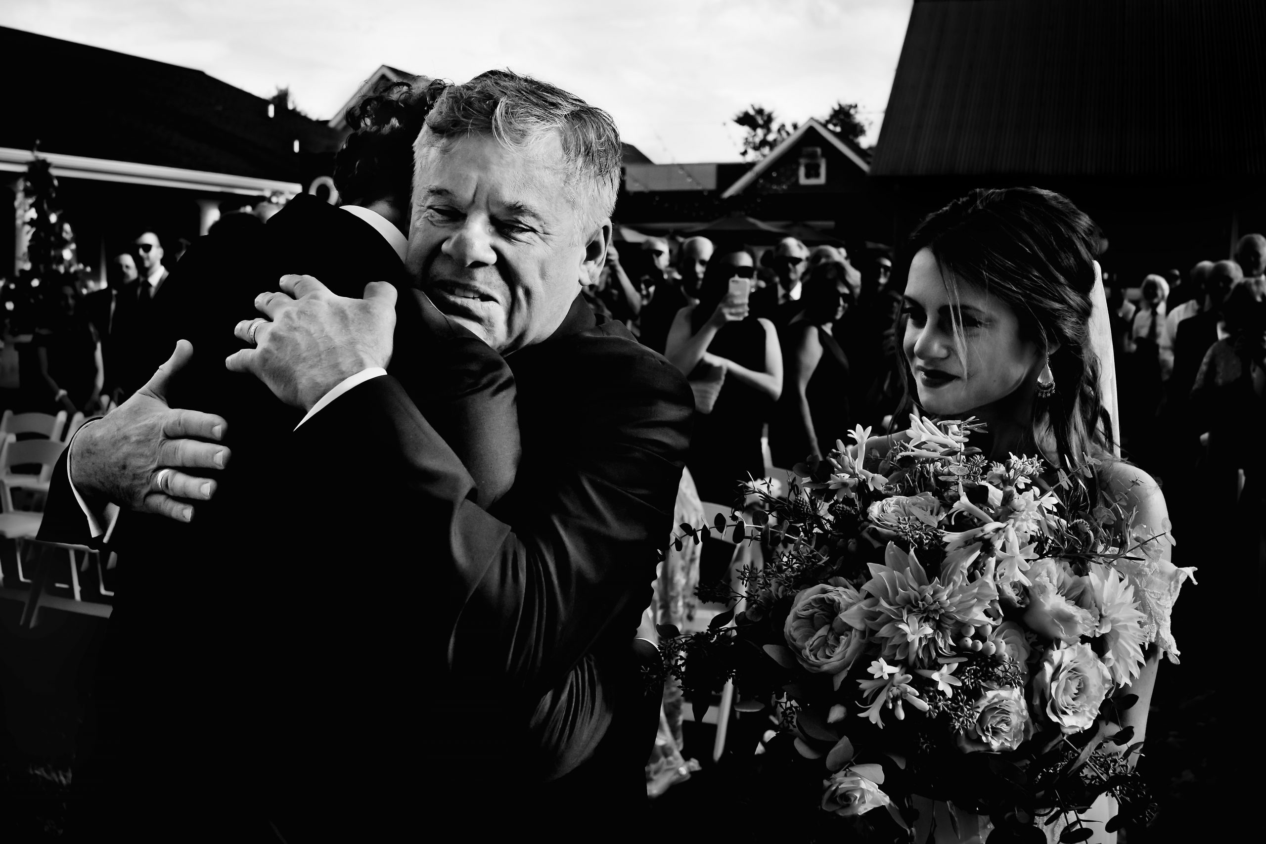Bride's father hugs the groom at the wedding ceremony