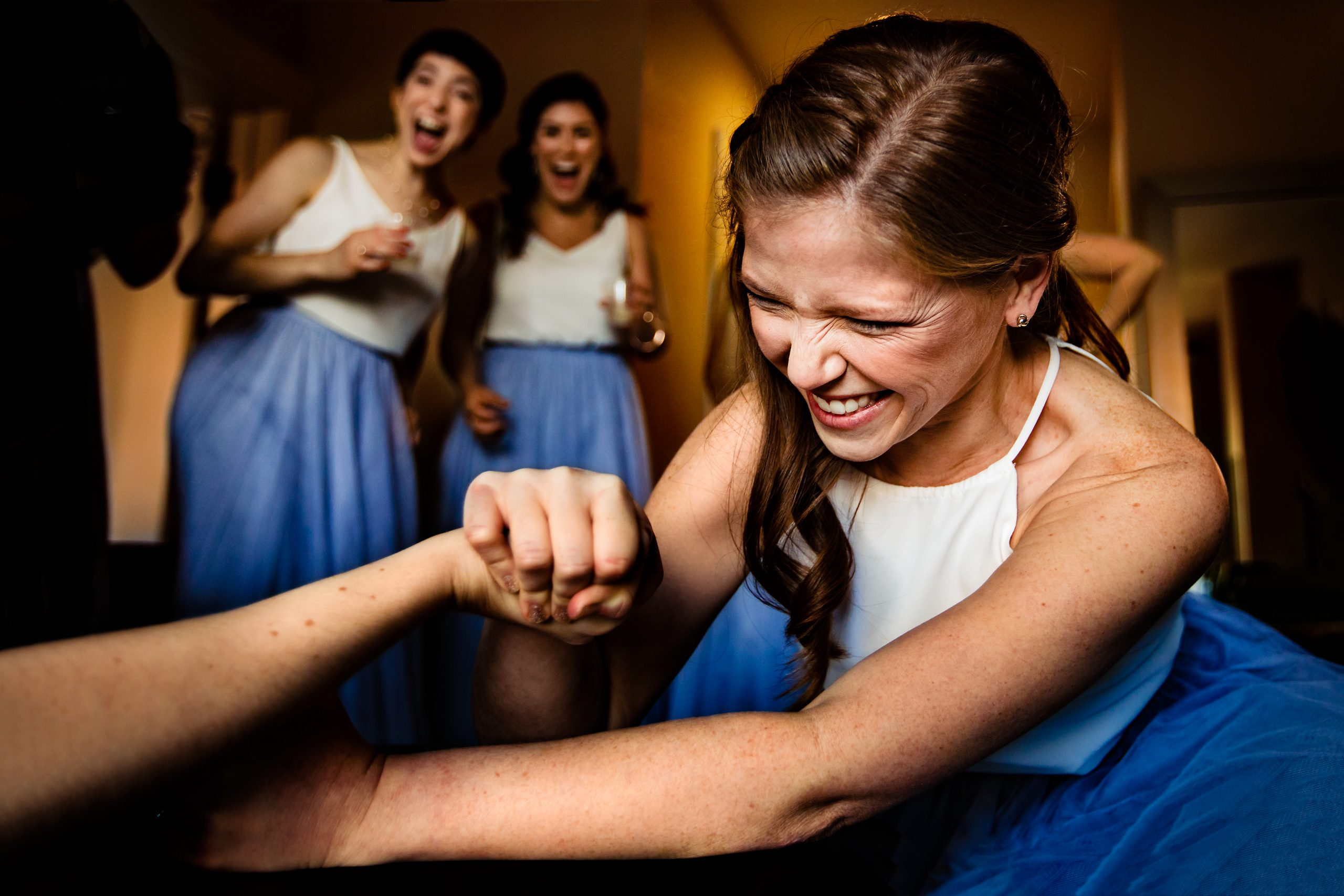 Bridesmaid struggles to win arm wrestle as other bridesmaids cheer