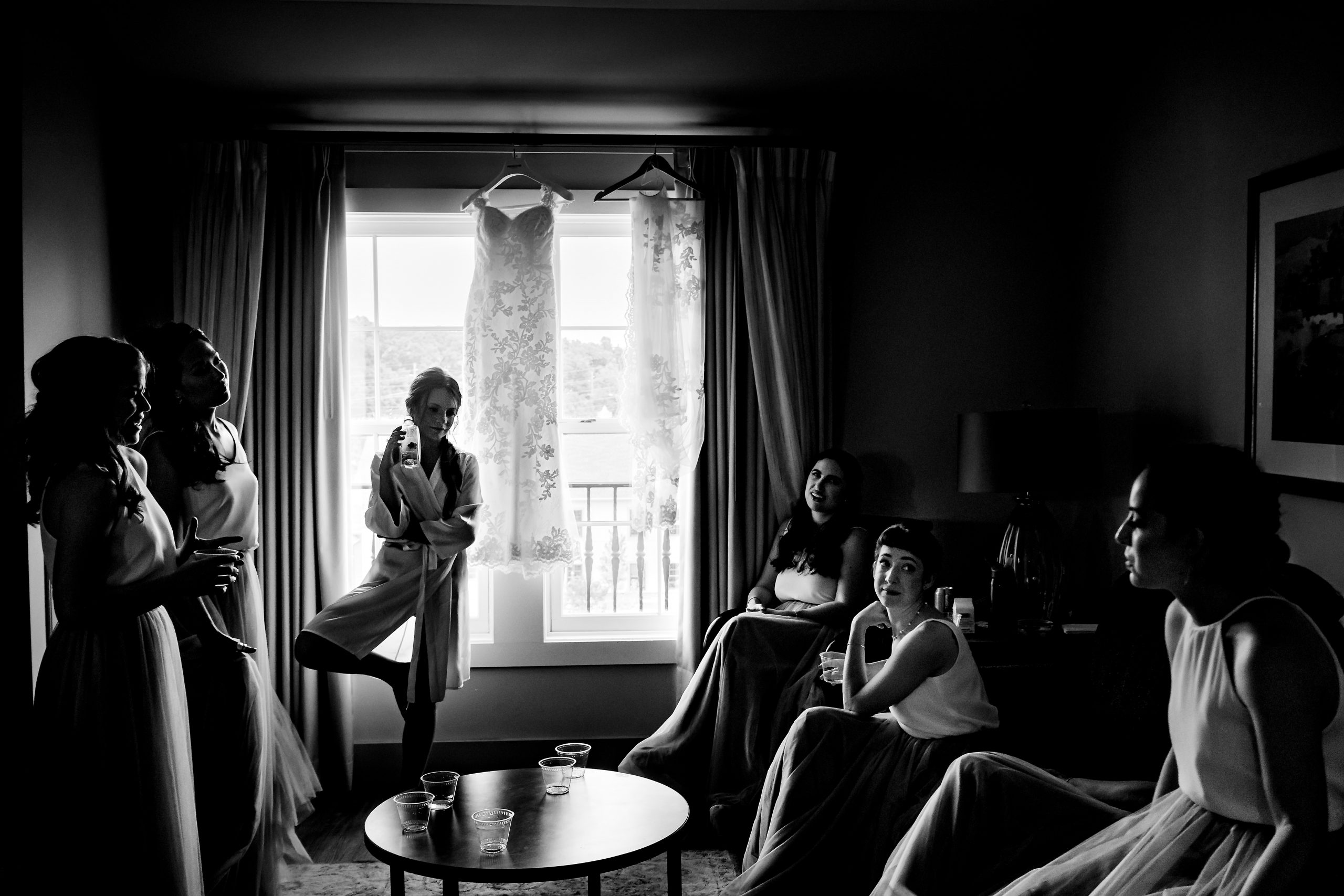 Bride and her bridesmaids sit around a room chatting