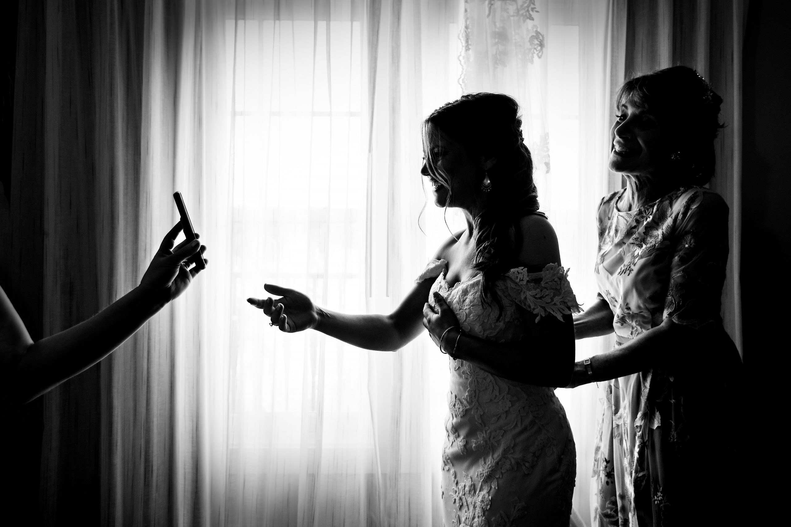 A bride and her mom smile as they react to a phone