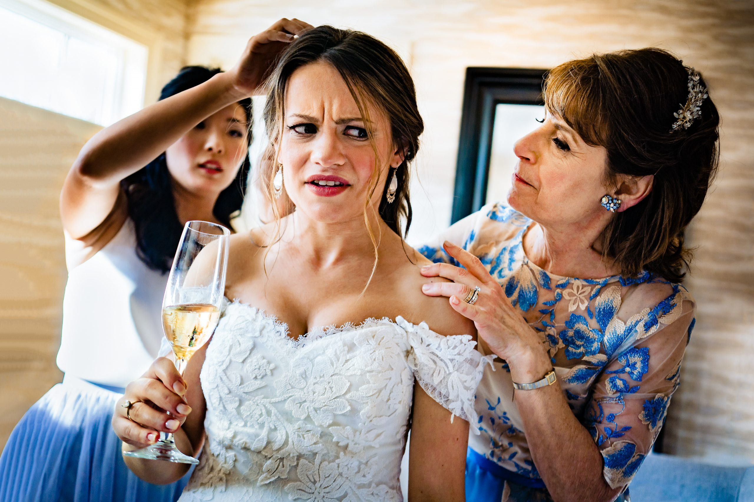 Bridesmaid and the bride's mother fix the bride's hair while she holds a flute of Champagne