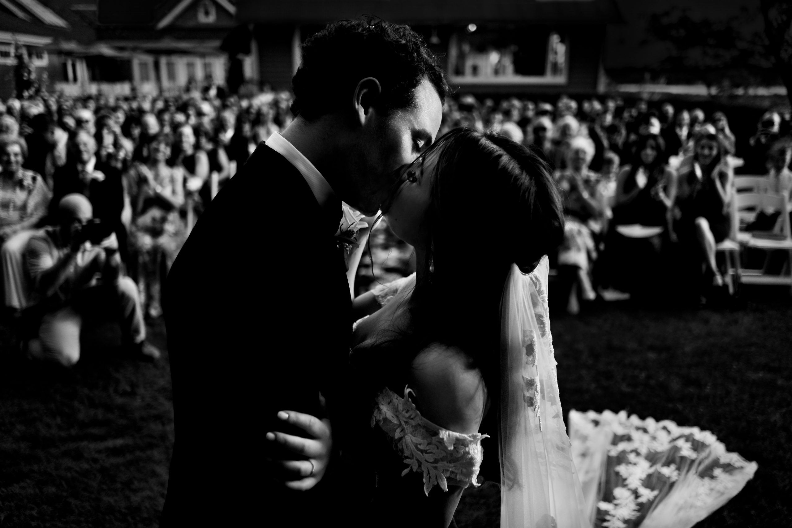 Weddings guests clap as the bride and groom kiss for the first time as husband and wife
