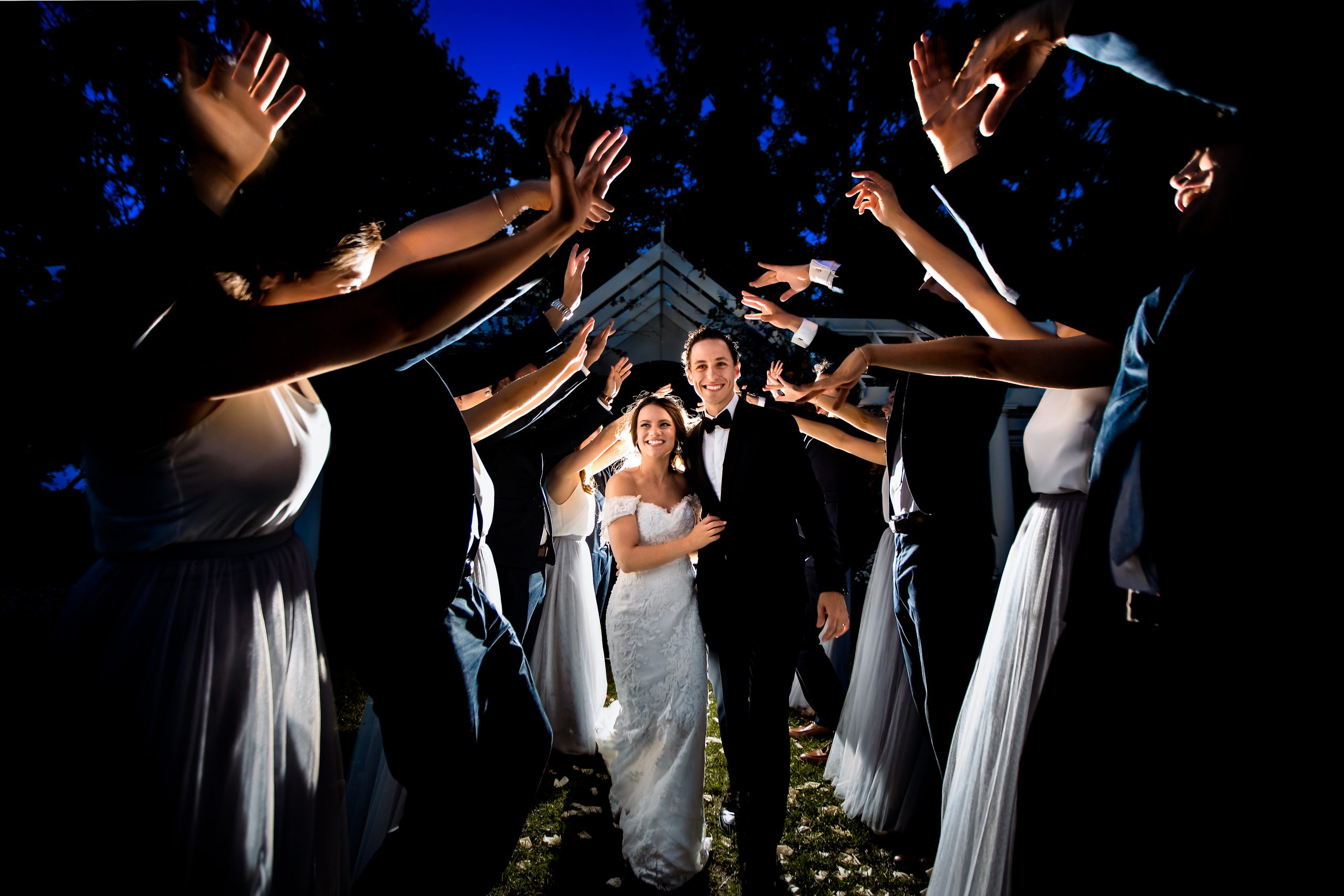Weddings guests raise their arms as the bride and groom walk back down the aisle